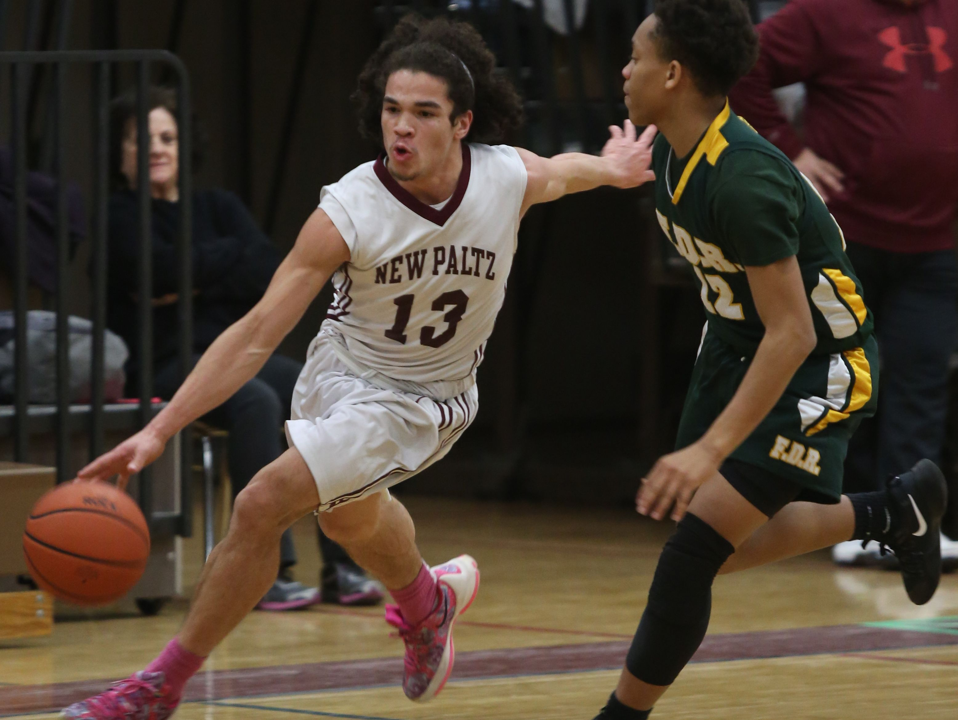New Paltz's Axel Rodrigues (13) dribbles the ball past Franklin D. Roosevelt's Kevin Henri (12) during basketball game at New Paltz High School on Feb. 3, 2017.