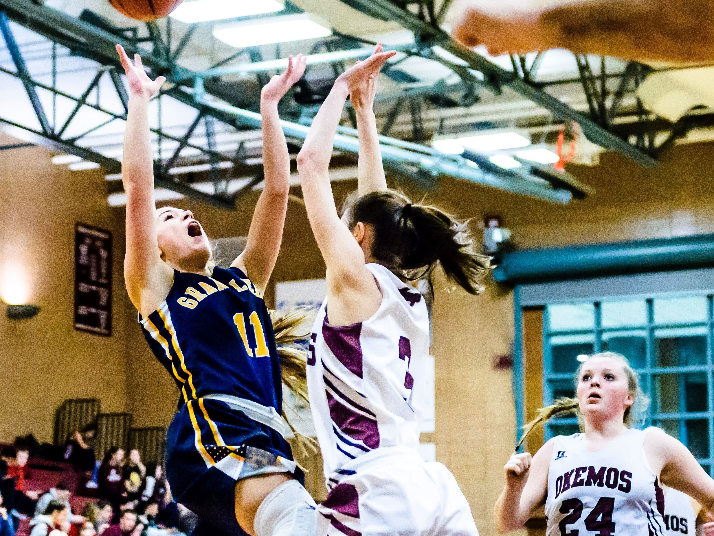 Brooke Rambo, left, of Grand Ledge puts up a shot over Skylar Westfall of Okemos during their game Friday February 3, 2017 in Okemos. Westfall was charged with a foul on the play.