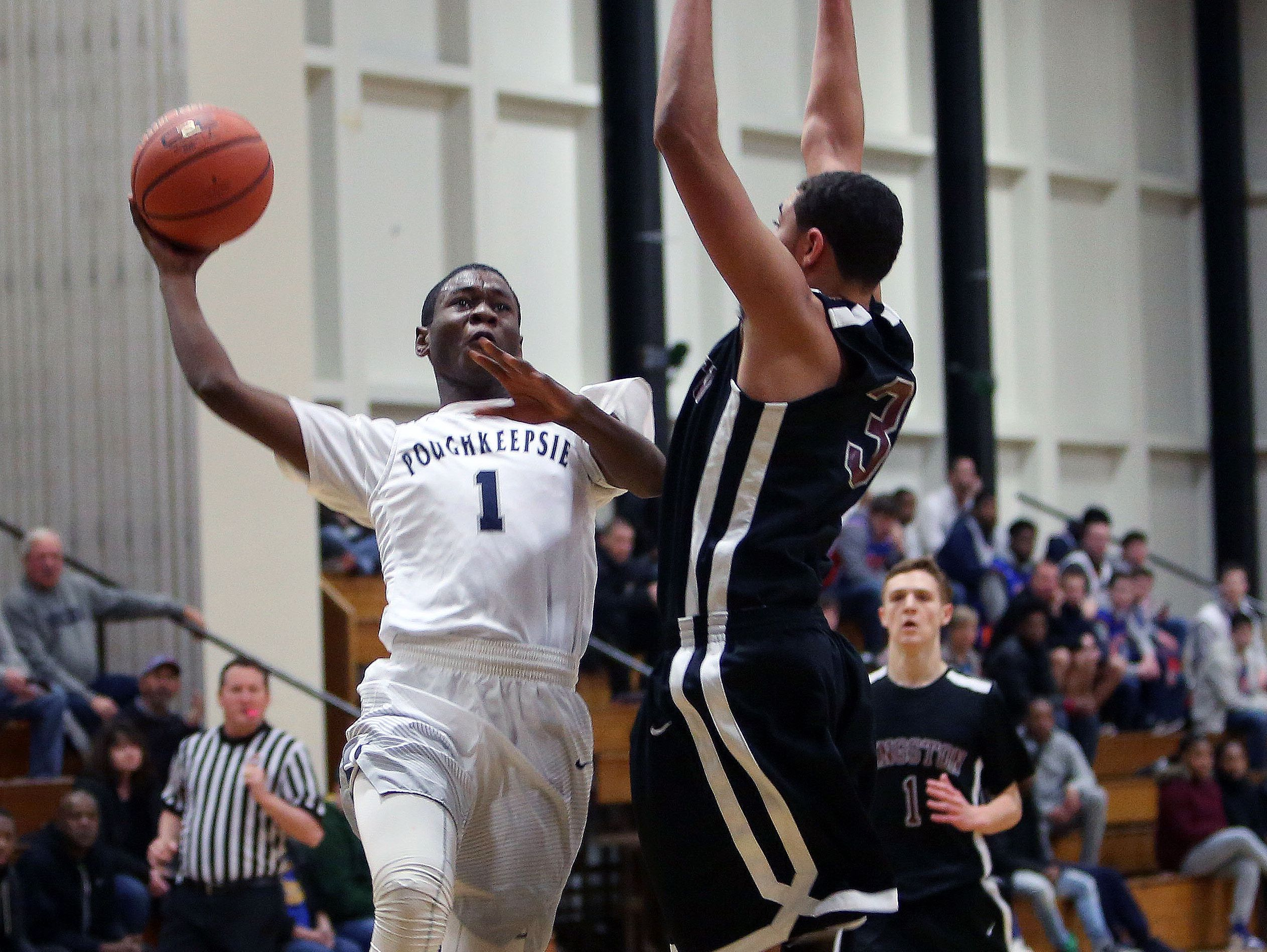 Poughkeepsie's Shaquez Nesbitt (1) drives to the basket in front of Kingston's Skilar Ryan (30) during the Officials vs Cancer basketball tournament at Dutchess Community College Feb. 4, 2017. Kingston won the game 66-46.