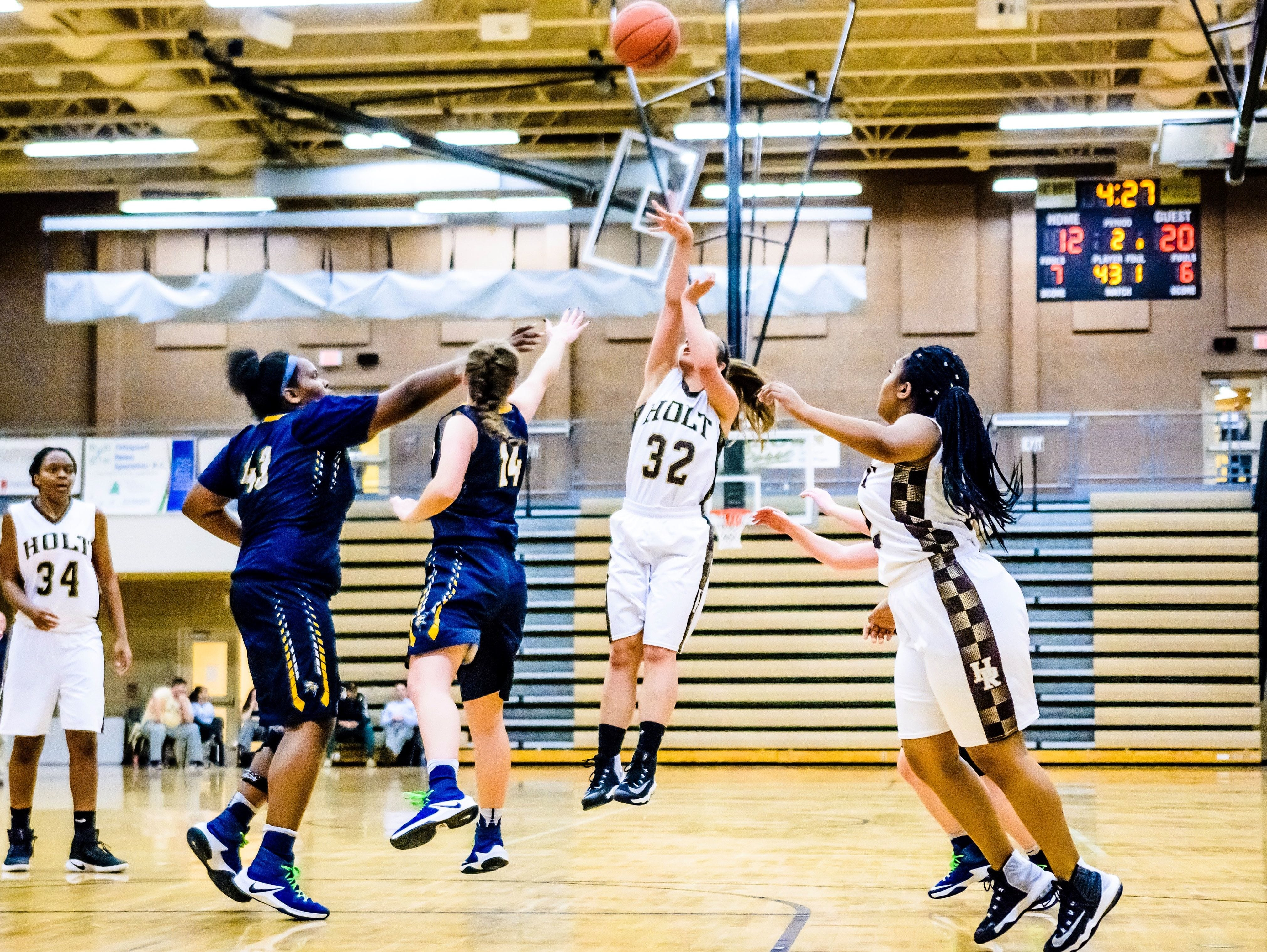 Alliyiah Demmers ,32, of Holt knocks down a 3-point shot over Haslett defenders during their game Tuesday February 7, 2017.