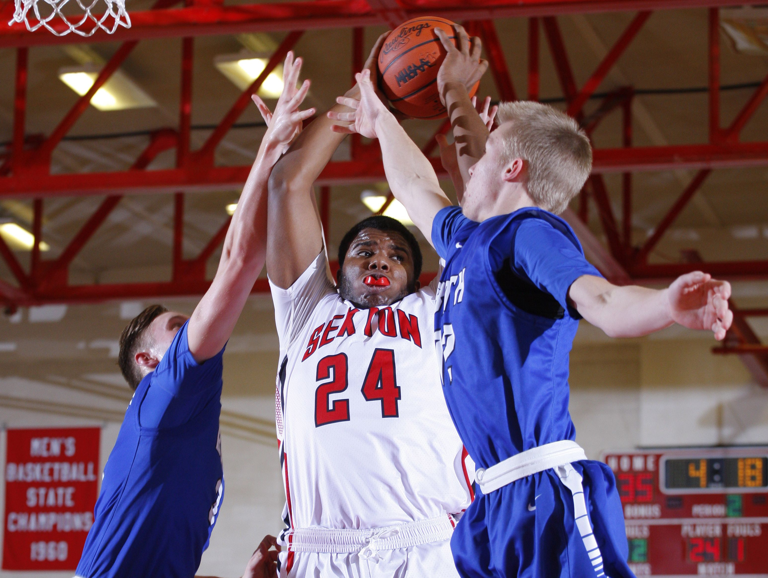 Sexton's D'Carlo Manuel (24) and Bath's Max Tiraboschi, left, and Jacob Deveau, right, vie for a rebound Tuesday, Feb. 7, 2017, in Lansing, Mich. Sexton won 82-39.
