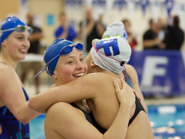Ali Terrell (left) hugs Jessie Fraley (right), after the 100 backstroke final.