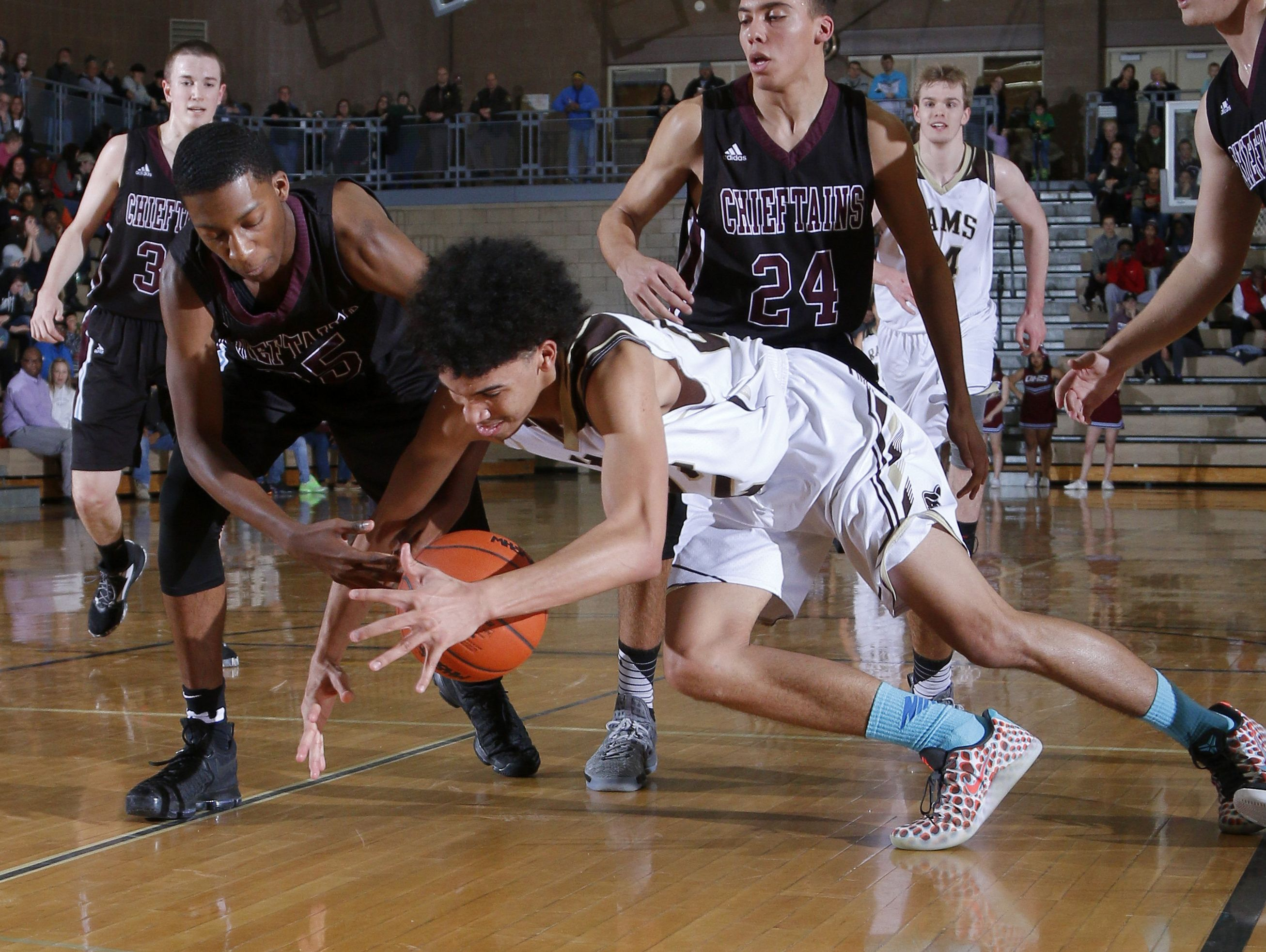 Holt's Deandre Whetstone, right, and Okemos' Collyn Richardson dive for a loose ball Friday, Feb. 10, 2017, in Holt, Mich. Holt won 94-86 in overtime.