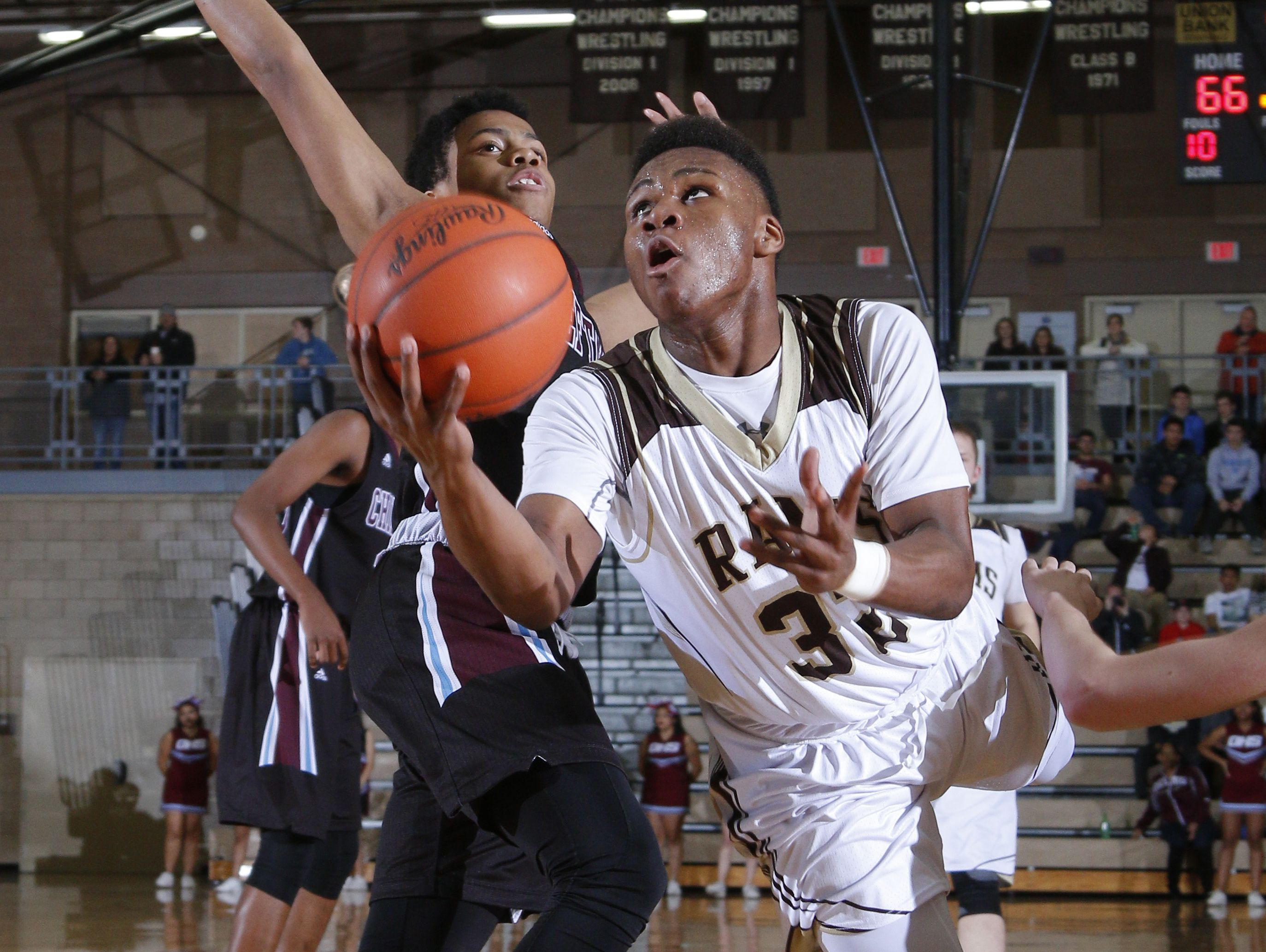 Holt's Ar'tavious Kibng, right, puts up a layup against Okemos' Noah Pruitt Friday, Feb. 10, 2017, in Holt, Mich. Holt won 94-86 in overtime.