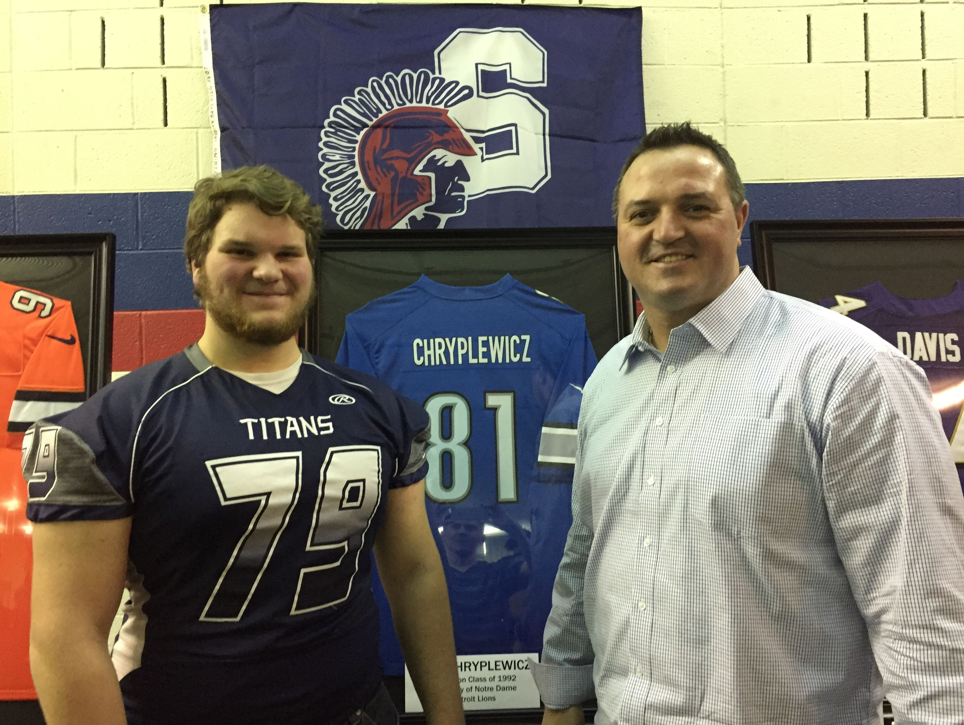 Former Sterling Heights Stevenson and Detroit Lions standout Pete Chryplewicz takes a picture with Stevenson junior Jacob Henry during a jersey ceremony in Sterling Heights on Jan. 26, 2017