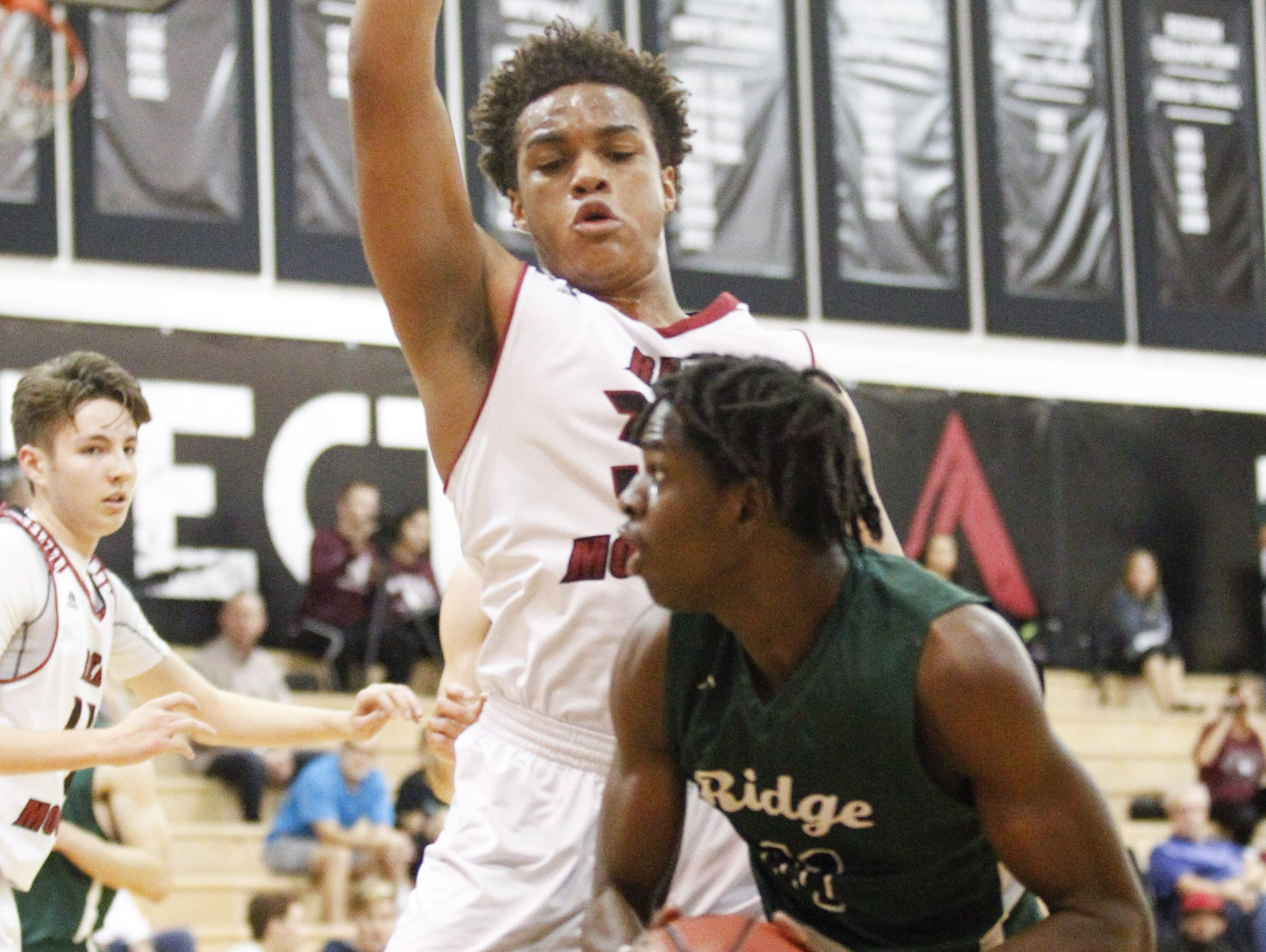 Mountain Ridge's Saikou Gueye (11) goes up for a layup as Red Mountain's Andre Harris (30) defends in the first half at Red Mountain High School in Mesa on Friday, Feb. 10, 2017.