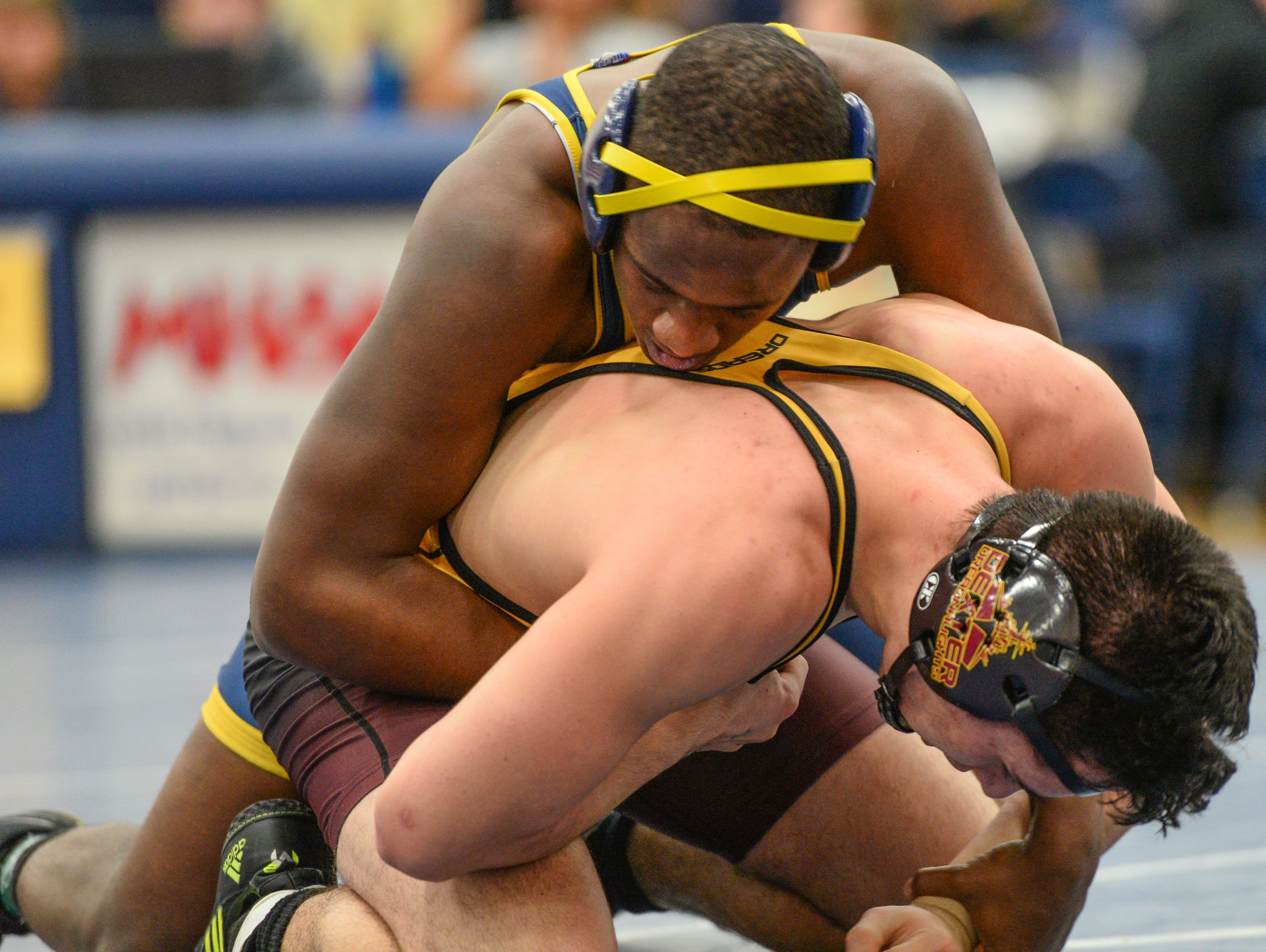 Eastern's Andwele Pulliam, top, over-powers Austin Aceves from Dexter and wins 12-3 in the 171 weight class at the D2 District tournament held at DeWitt Saturday, February 11, 2017.