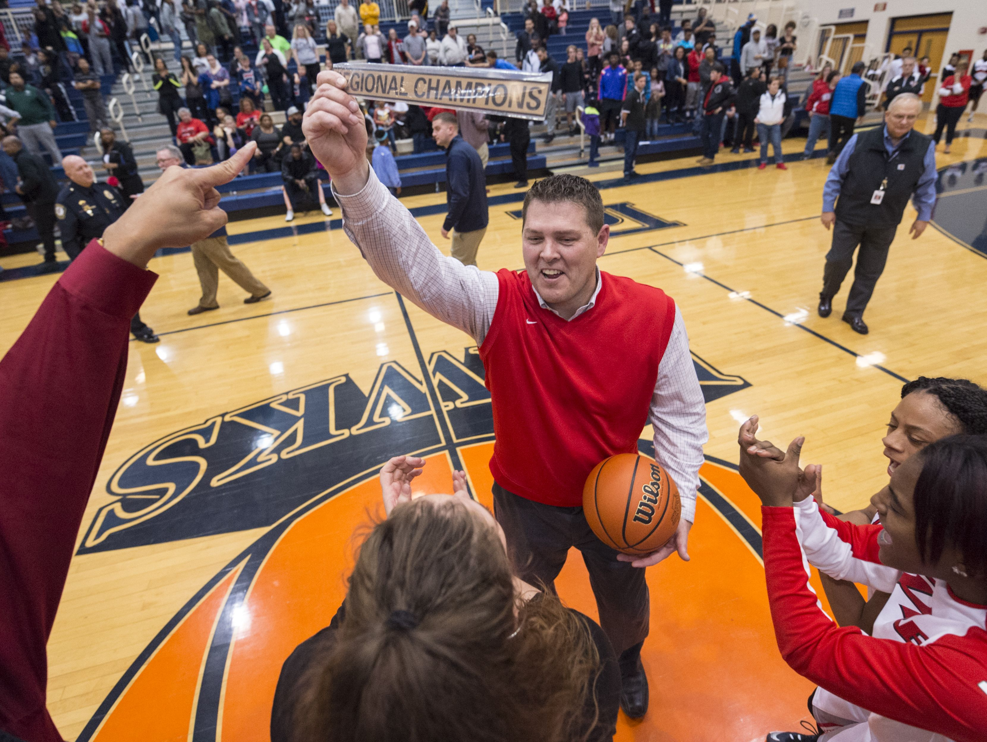 Pike coach Bob Anglea celebrates with the Regional Champions trophy and the game ball after winning the IHSAA 4A Girls' Basketball Tournament Regional championship game, Saturday.