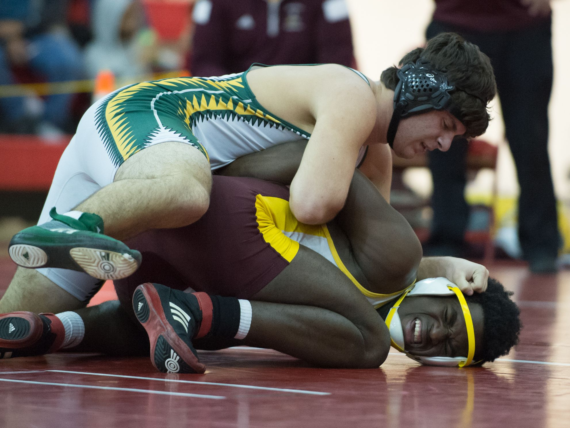Milford's Bevensky Augustine works to get out from a hold by Indian River's John Keller in the 182 pound match at DIAA Dual Meet Wrestling State Championship at Smyrna High School.