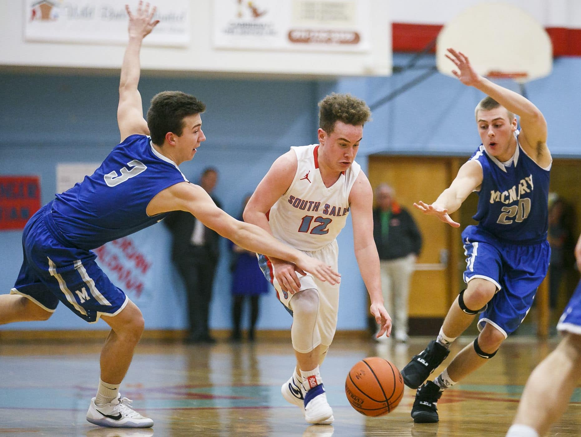 South Salem's Trey Galbraith (12) dribbles through McNary's Andrew Jones (3) and Cade Goff (20) in a game on Tuesday, Feb. 14, 2017. South Salem won the home game 81-71 over McNary.