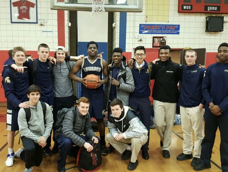 Our Lady of Lourdes High School's James Anozie poses with basketball teammates after scoring his 1,500th career point on Tuesday.
