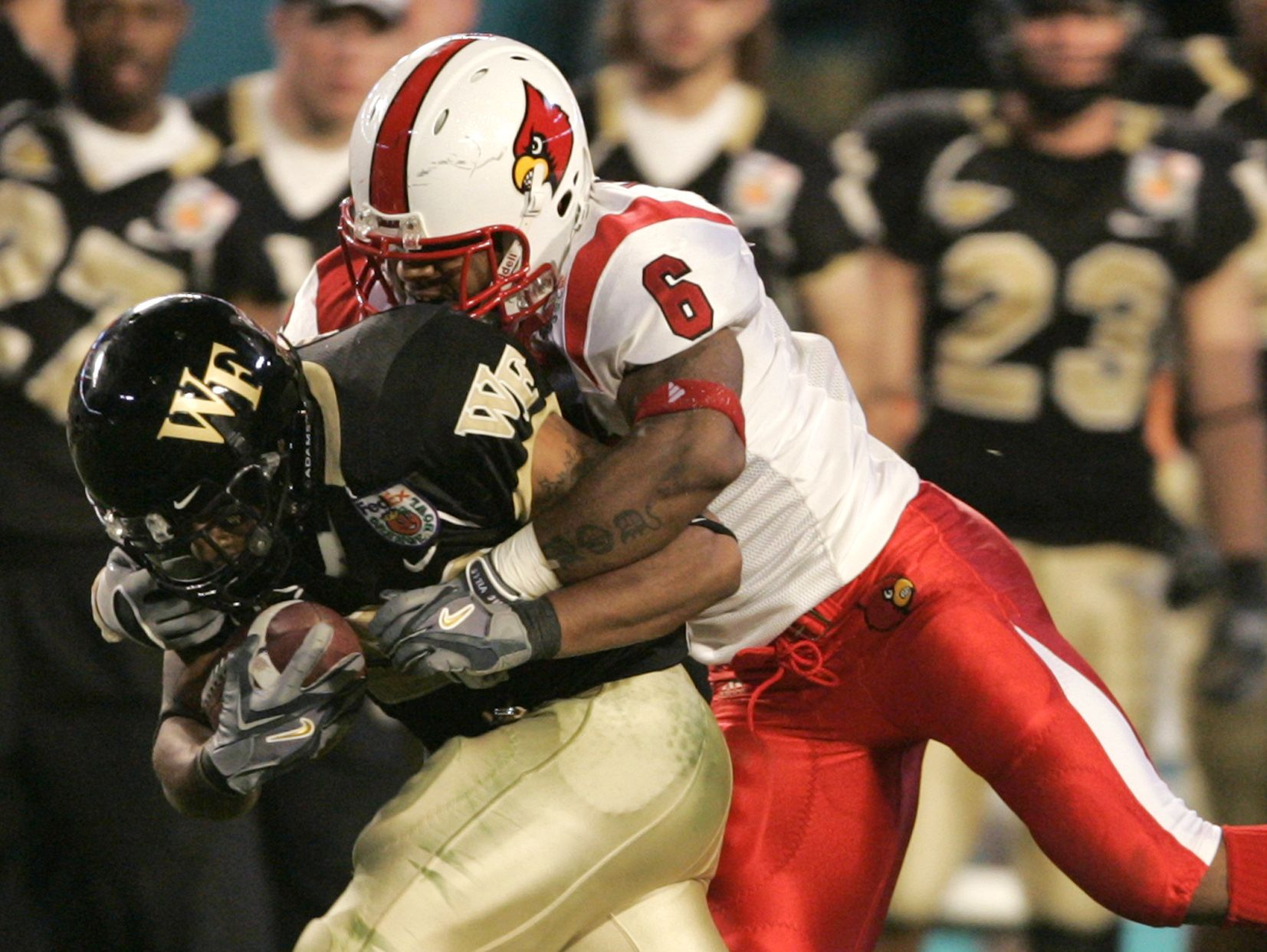 Louisville's Preston Smith (6) brings down Wake Forest running back Kenneth Moore in the third quarter of the Orange Bowl football game Tuesday, Jan. 2, 2007, in Miami. (AP Photo/Lynne Sladky)