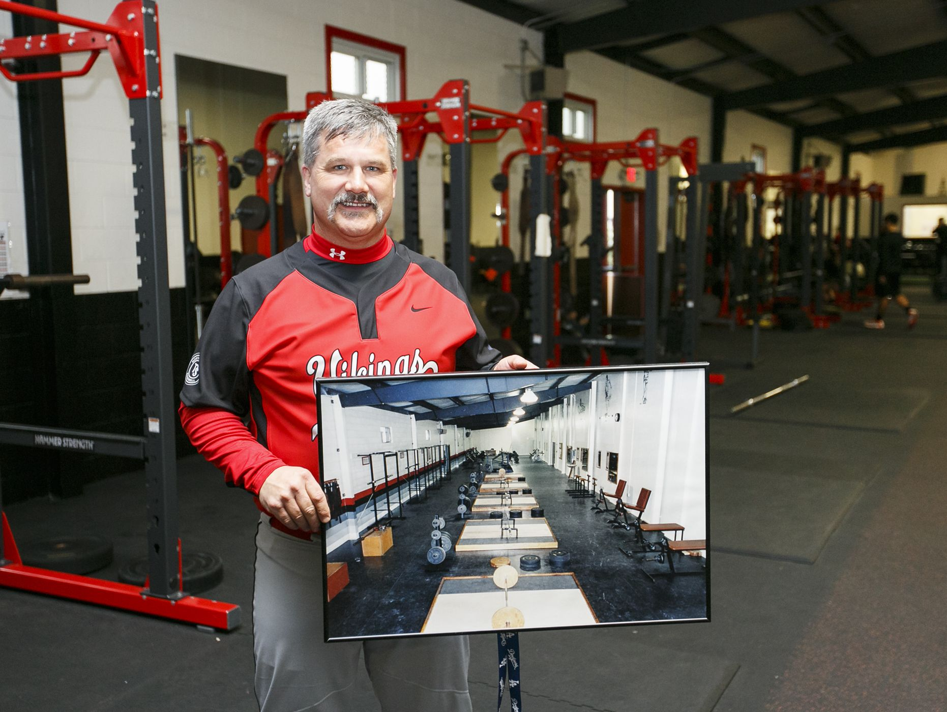 North Salem High School baseball coach Chris Lee holds a photo of the weight room taken in 1992 as he stands in the newly renovated room on Tuesday, Feb. 14, 2017. The room was considered state of the art when it was first built, but had started to show its age. Now the school has added new floors and equipment, with more improvements to come once they meet the rest of their $130,000 fund raising goal.
