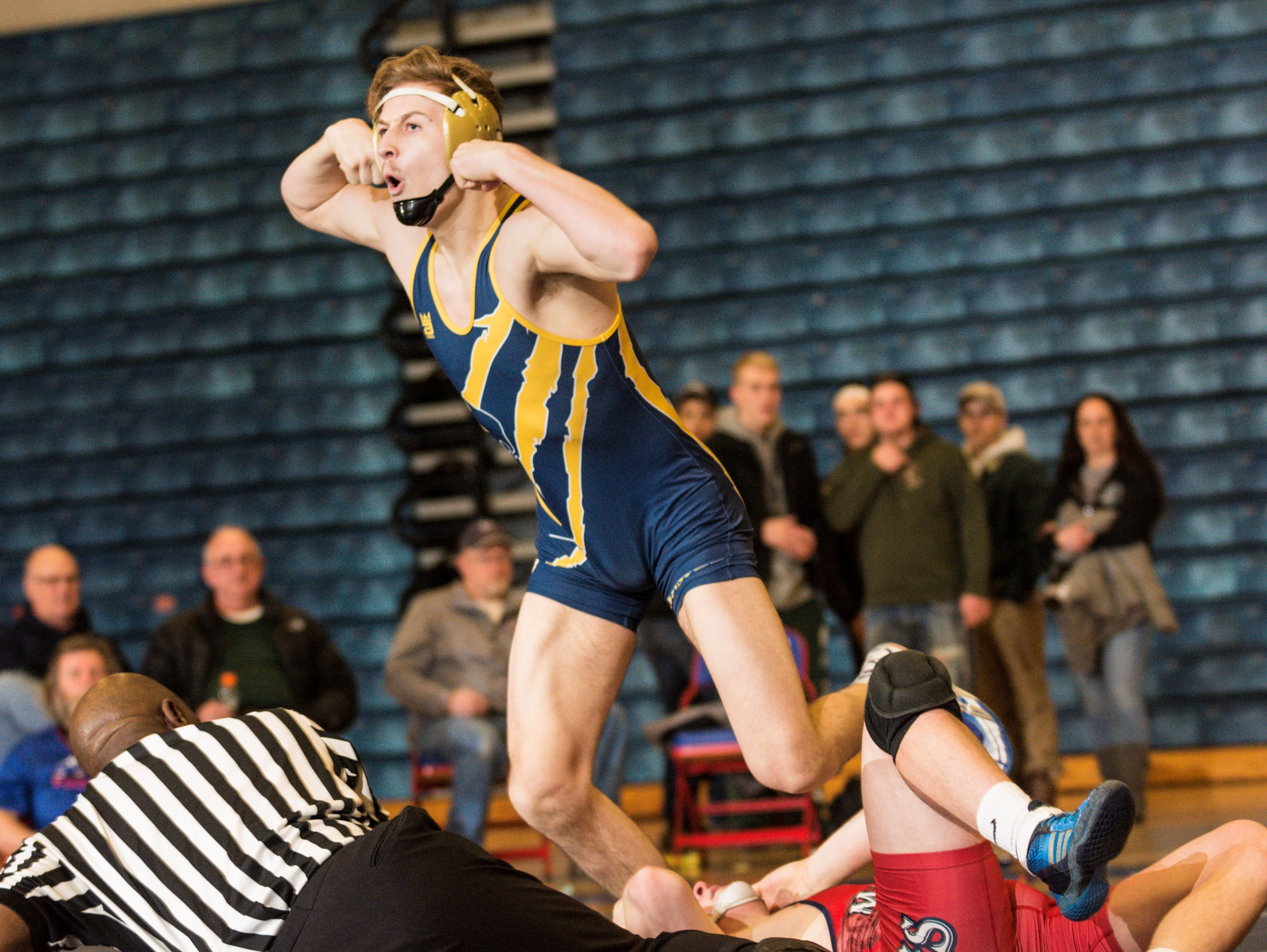 Sam York, top, of celebrates his pin of Jared Surato of Mason to end their 160lb. Division 2 regional final match Wednesday February 15, 2017 at Mason.