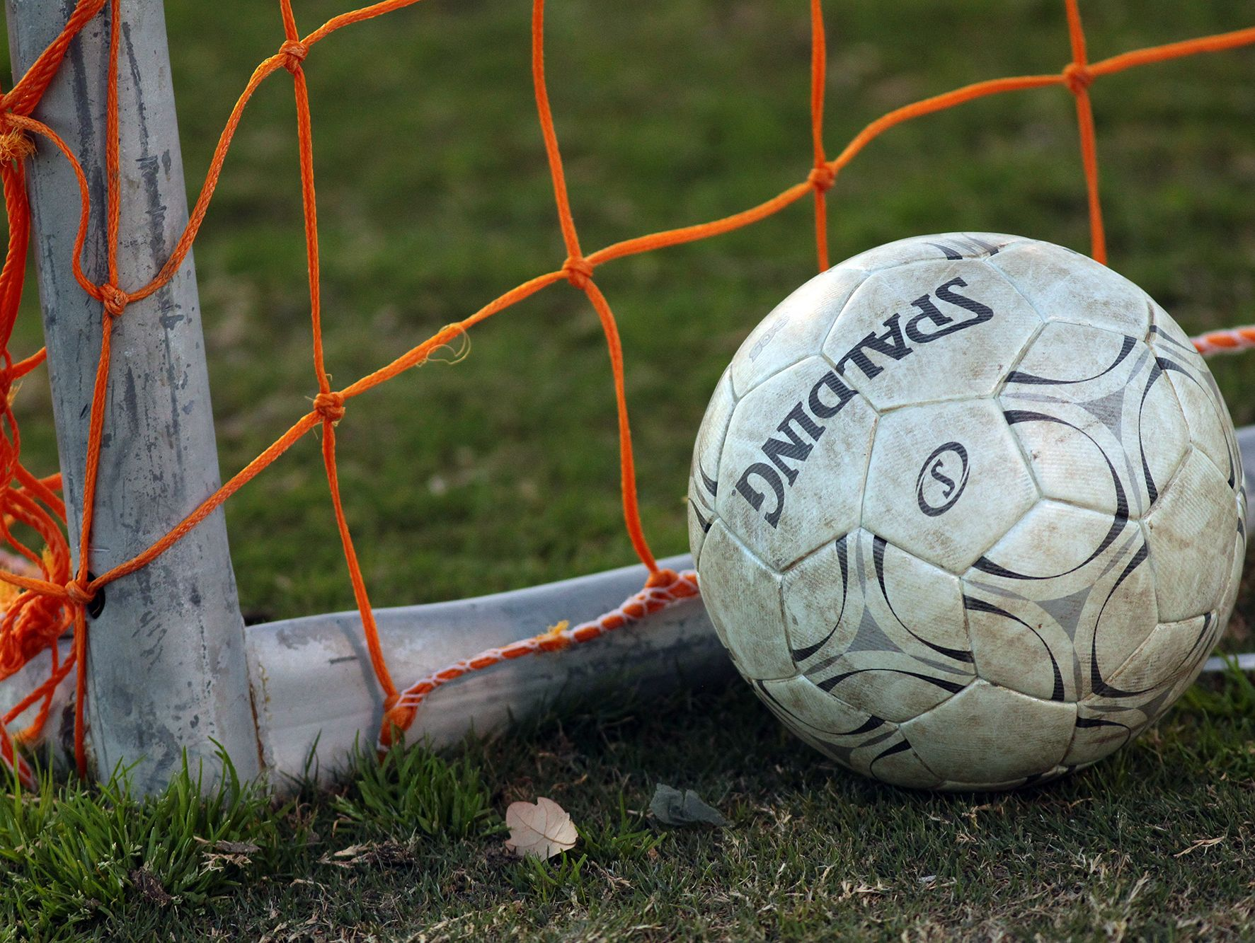 A soccer ball sits by the net during a high school soccer game.