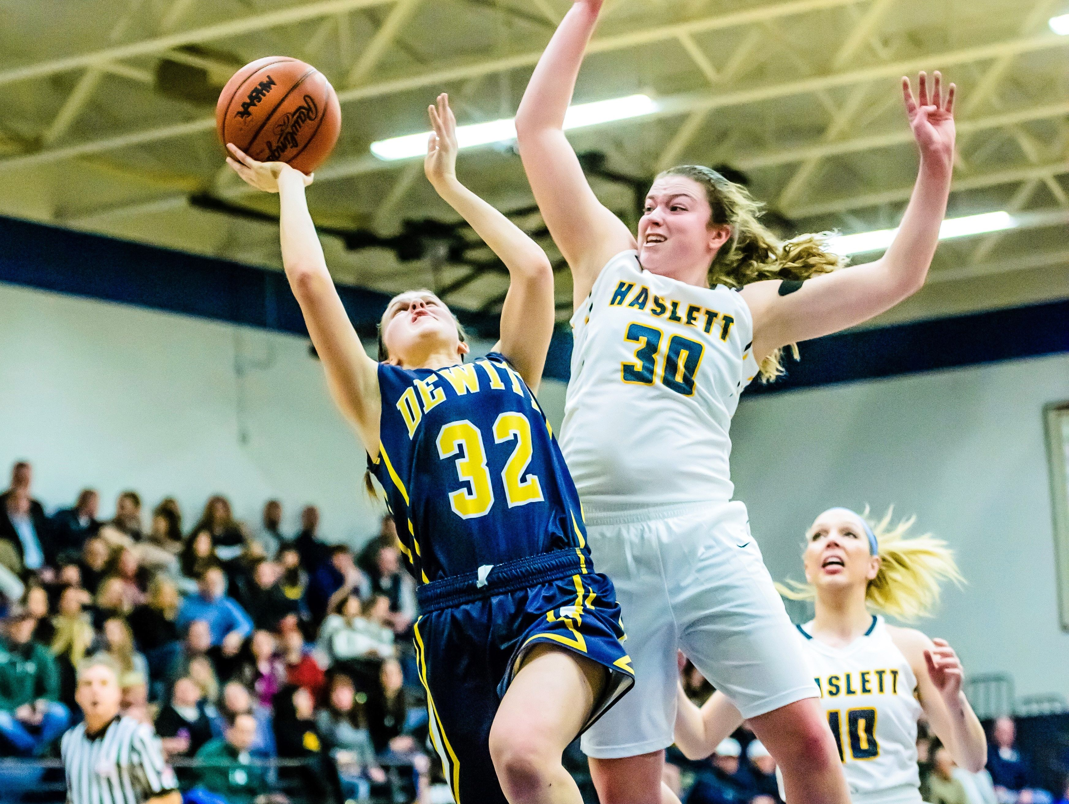 Sydnee Dennis ,30, of Haslett winds up to block a shot attempt by Jessah McManus of DeWitt during their game Friday February 17, 2017 in Haslett.