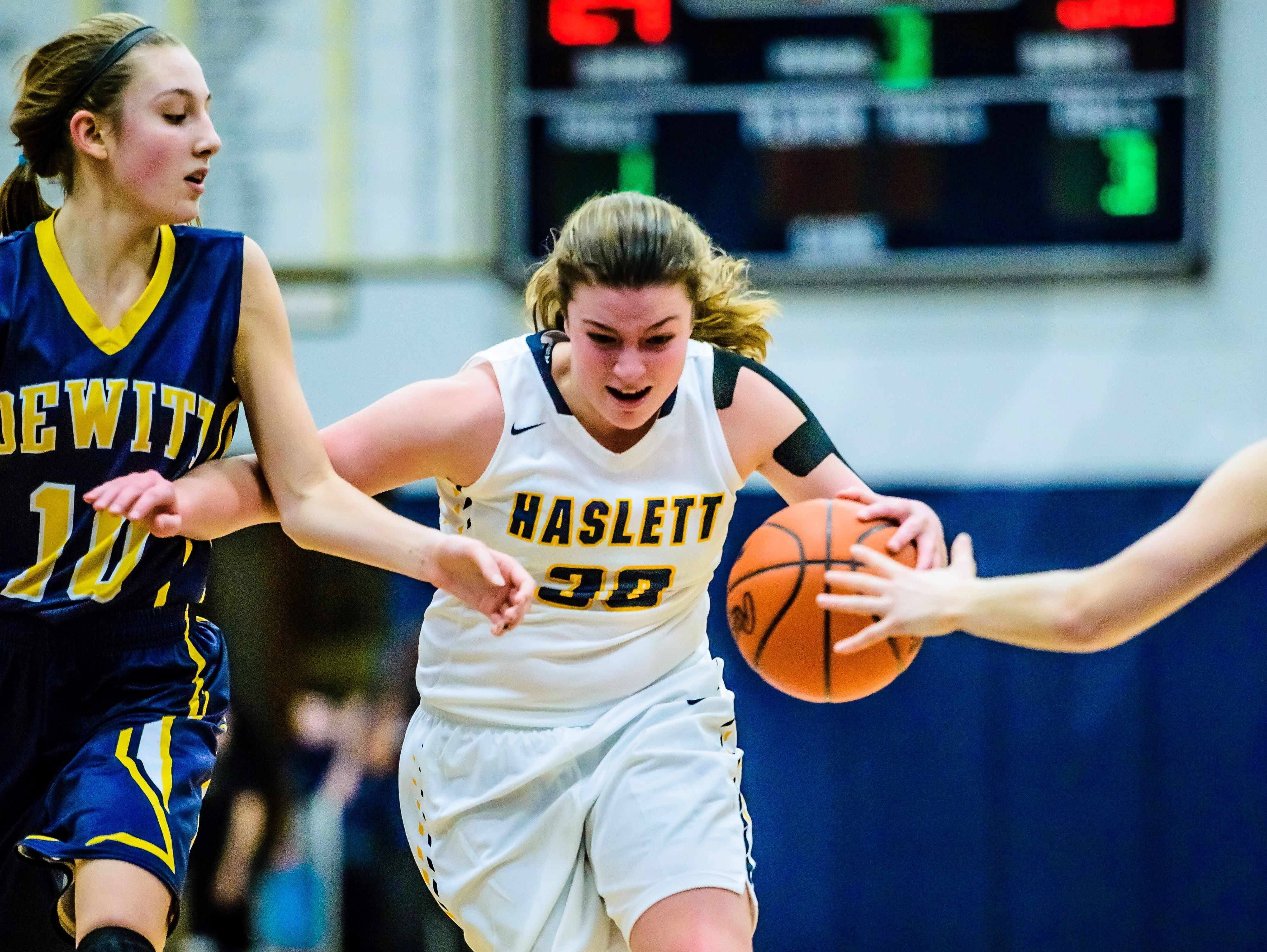 Sydnee Dennis, center, of Haslett drives into the paint while being defended by Sydney Mills ,10, of DeWitt with Haslett trailing by 4 late the 3rd quarter of their game Friday February 17, 2017 in Haslett.