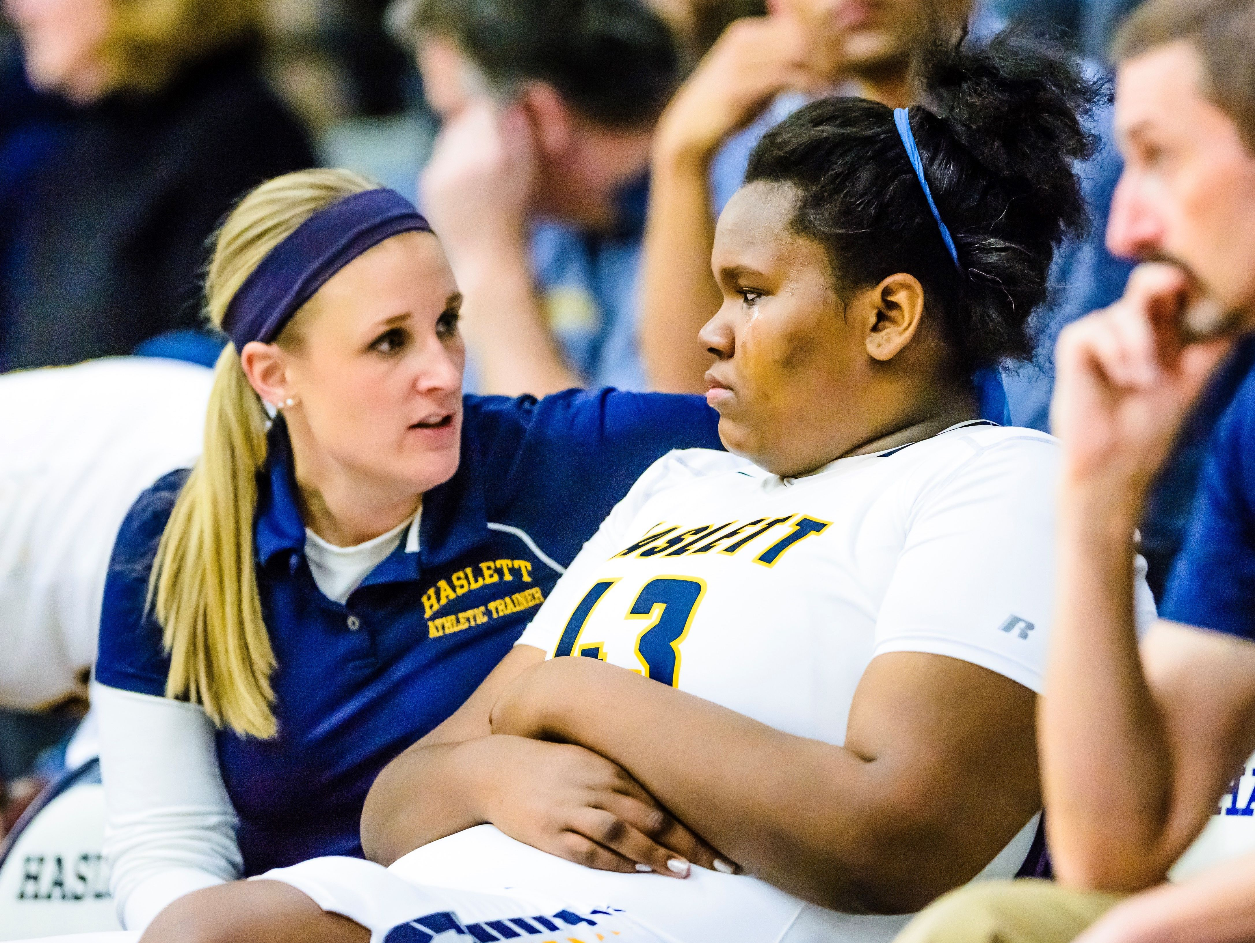 Imania Baker ,center, of Haslett sheds a tear as a Haslett athletic trainer discusses her head injury with her at halftime of the DeWitt/Haslett game Friday February 17, 2017 in Haslett. Baker suffered a head injury in the 1st quarter and after a brief reappearance in the 2nd quarter, left the game not to return.