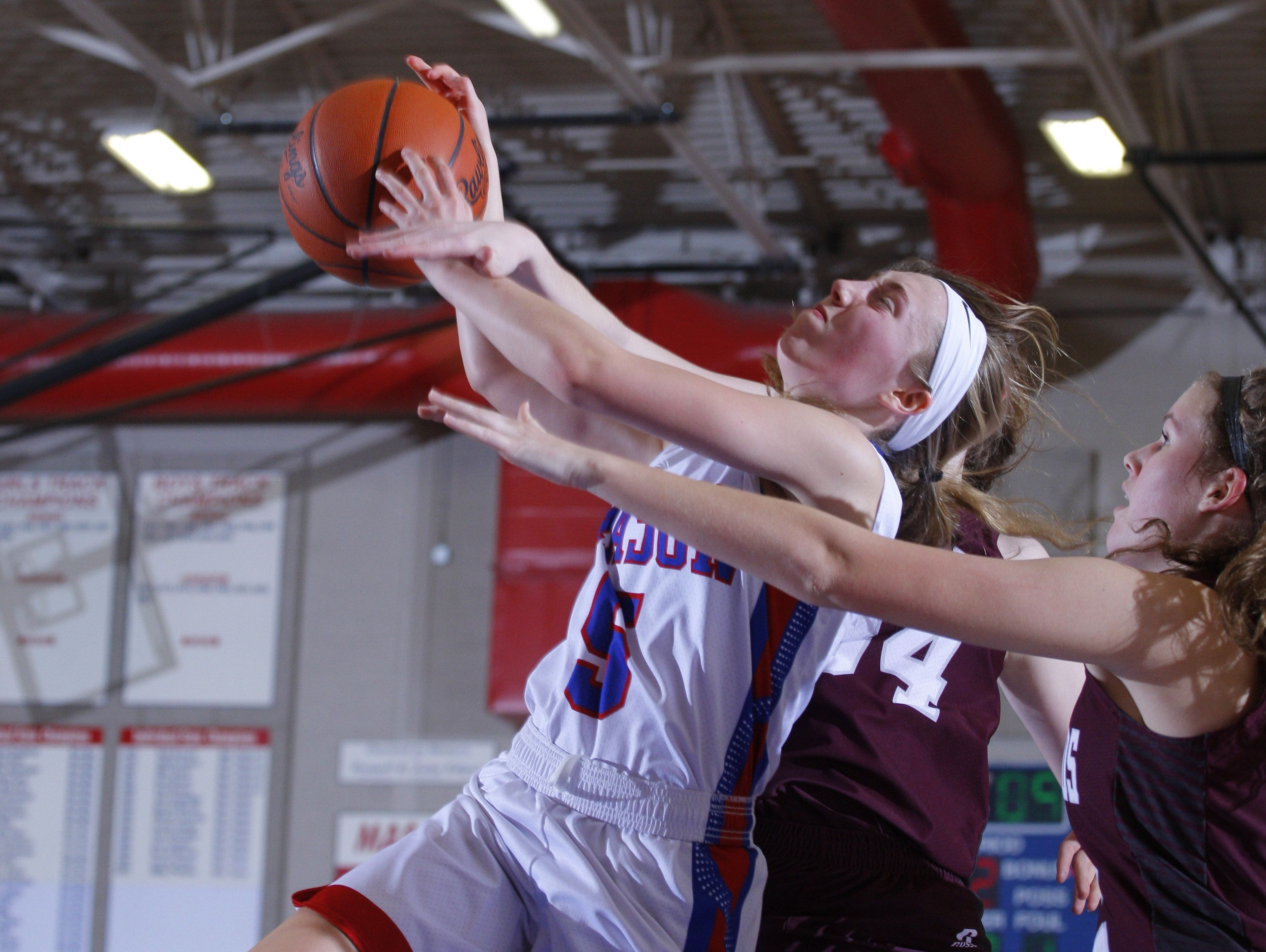 Mason's Katherine Rochon, left, and Eaton Rapids' Anne-Marie Wright, center, and Samantha McDaniel fight for a rebound Tuesday, Feb. 21, 2017, in Mason, Mich.
