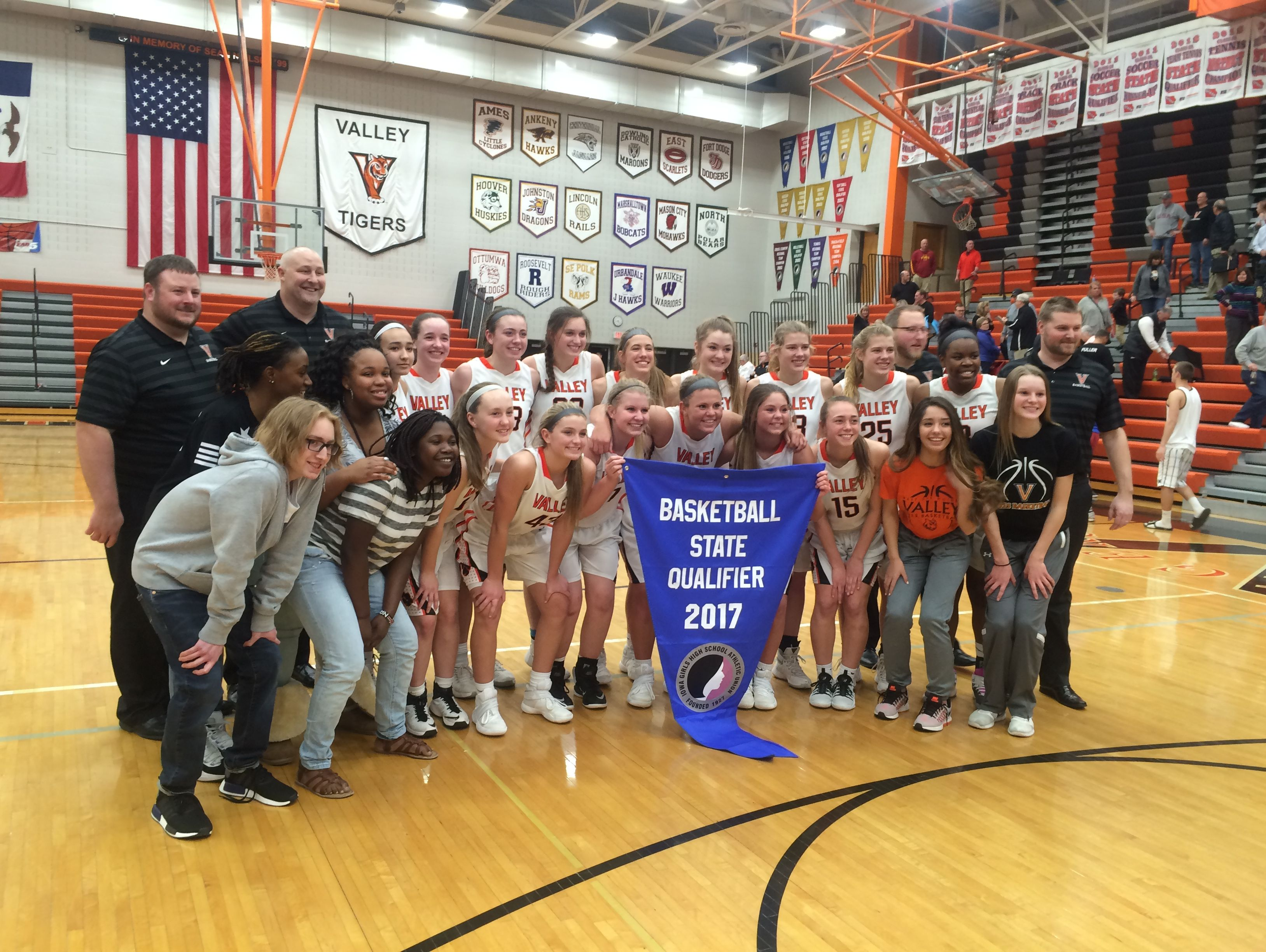 Valley's players pose with a state girls' basketball qualifier banner after beating Ames Tuesday.