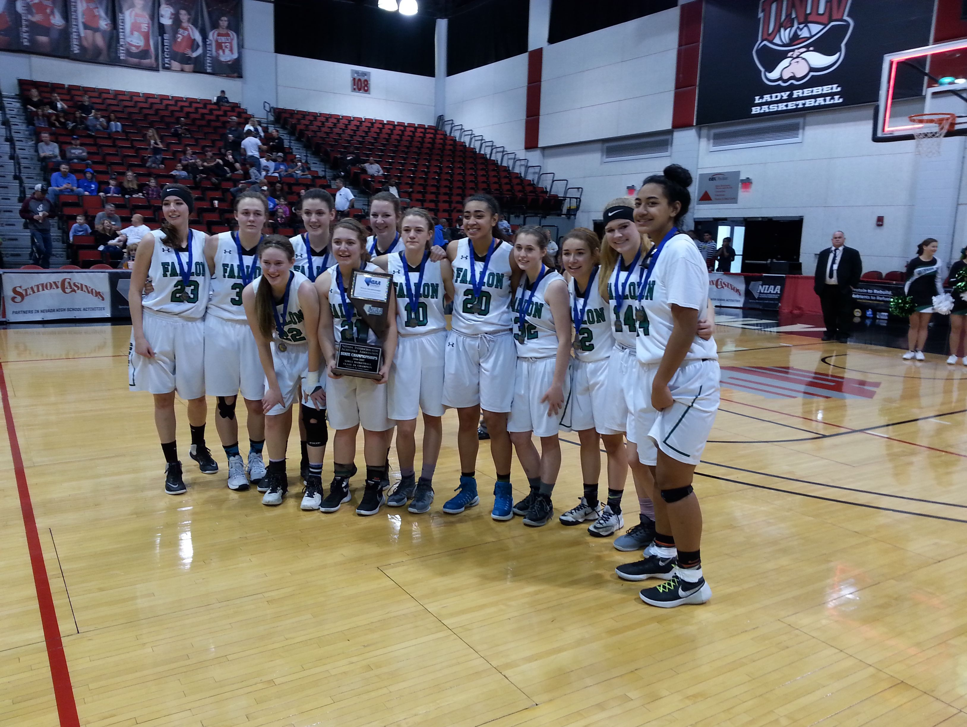 The Fallon players hold the trophy after the winning the state basketball championship Saturday in Las Vegas.