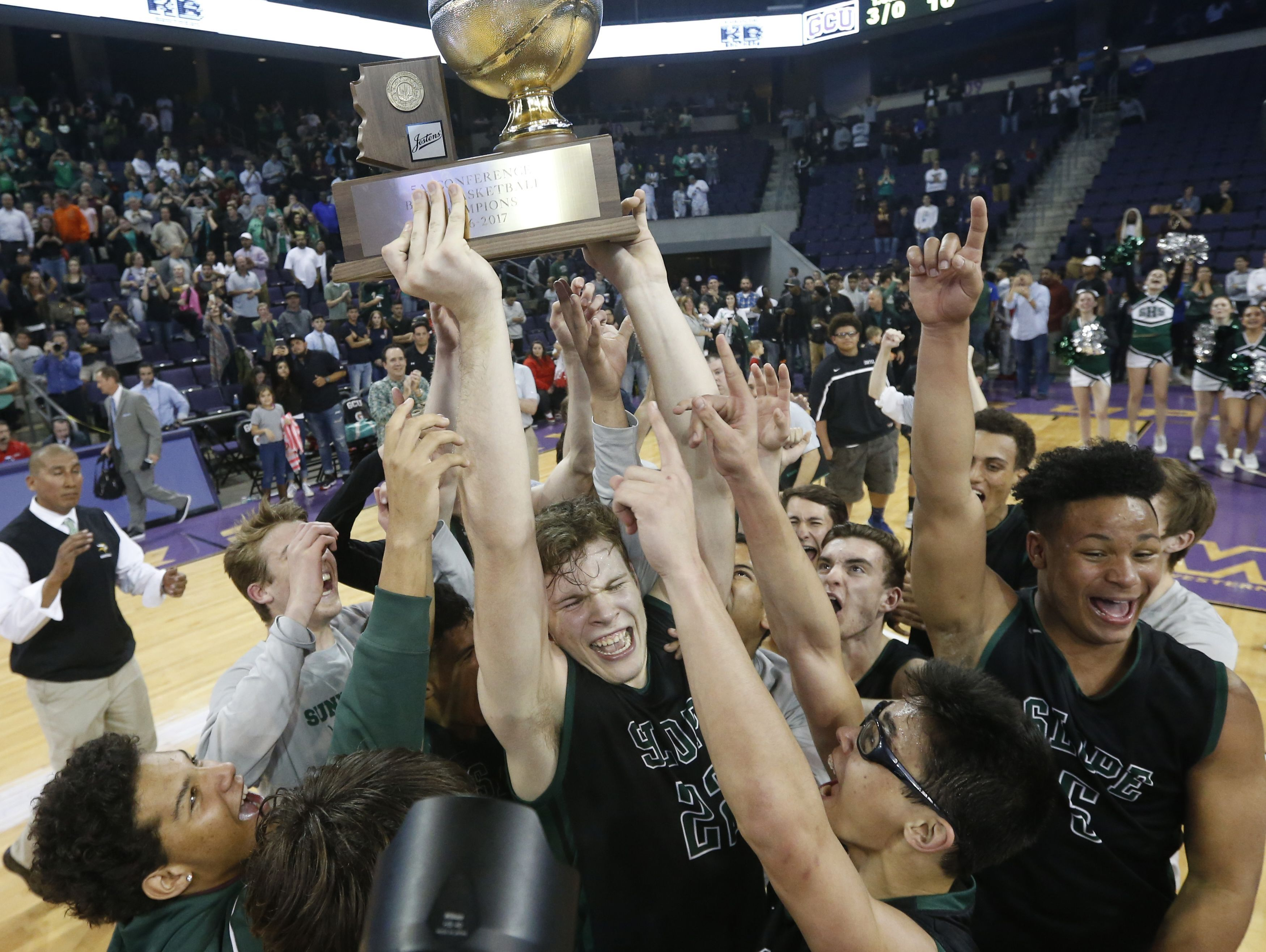 Sunnyslope's Chris Orozco (22) lifts the trophy with his team celebrating the State Championship win over Apollo, 58-57 in double overtime, at GCU Arena on February 27, 2017 in Phoenix, Ariz.