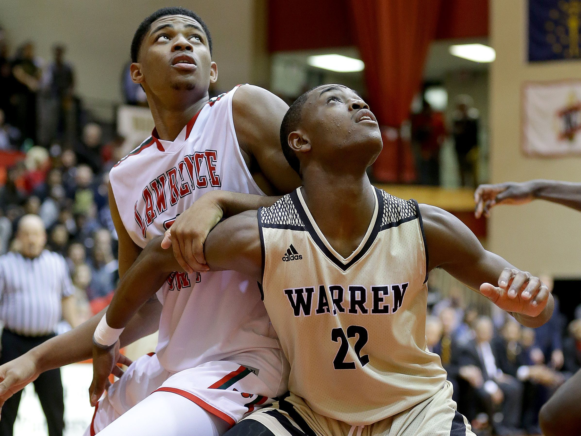 Lawrence North Wildcats Kevin Easley (34) and Warren Central Warriors Jakobie Robinson (23) fight for position under the basket in the second half of their game Tuesday, February 28, 2017, evening at North Central High School. The Lawrence North Wildcats defeated the Warren Central Warriors 60-54.