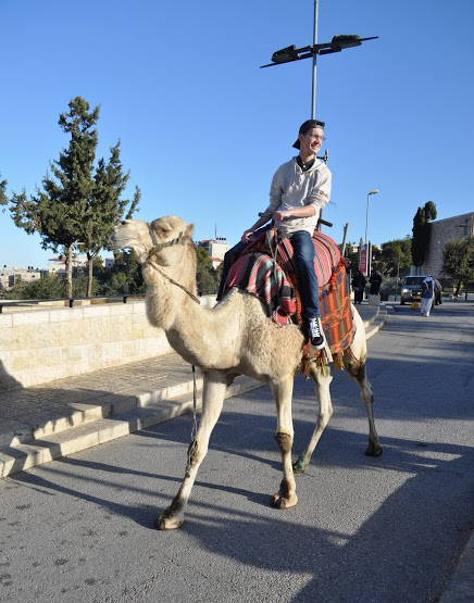 Andrew Lesnett riding a camel Credit: Bridget Stack