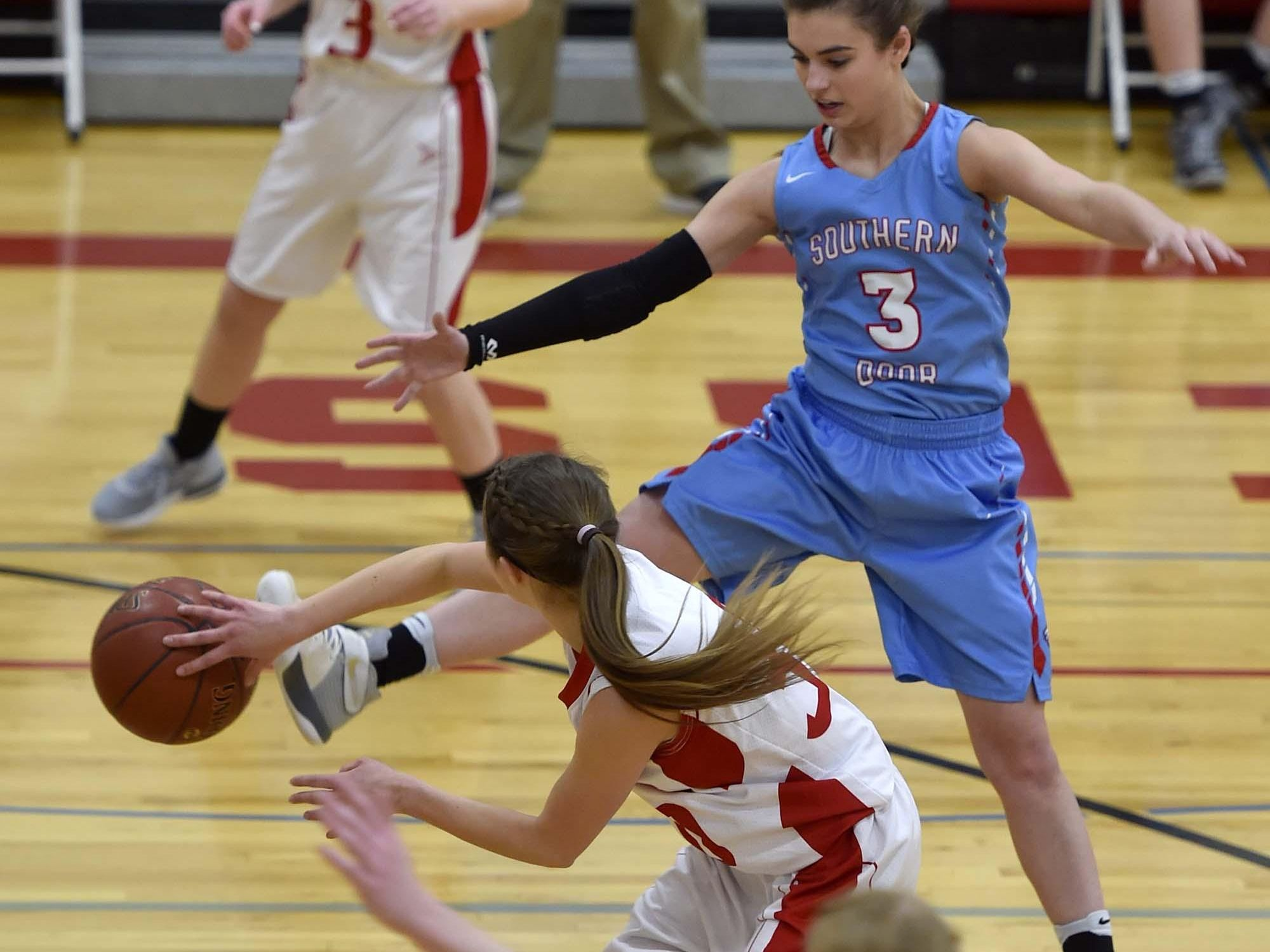 Sturgeon Bay's Allison Alberts passes ball around the outstretched leg of Southern Door's Gabby Atkins, right, to teammate Morgan Nelson during Friday's girls basketball game at Sturgeon Bay.