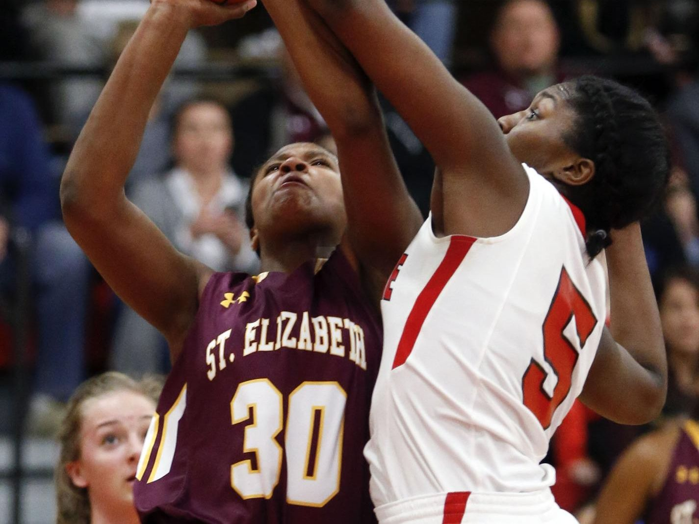 St. Elizabeth's Alanna Speaks (left) tries to shoot past the defense of Ursuline's Kay Wulah in Ursuline's 58-43 home win Wednesday.