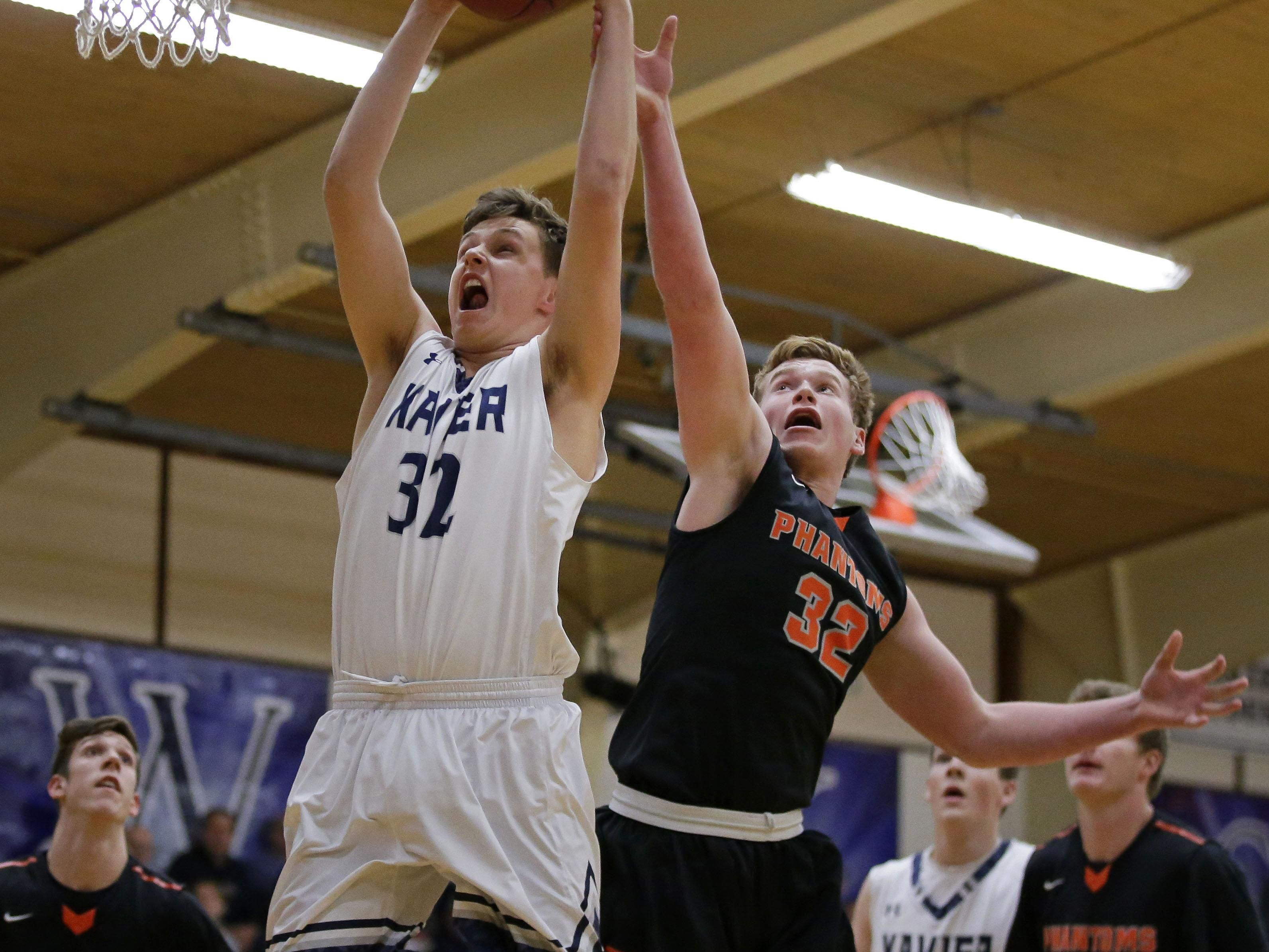 Will Schlicht of Xavier battles under the basket with Jake Karchinski of West De Pere on Thursday during a Bay Conference boys' basketball game in Appleton.