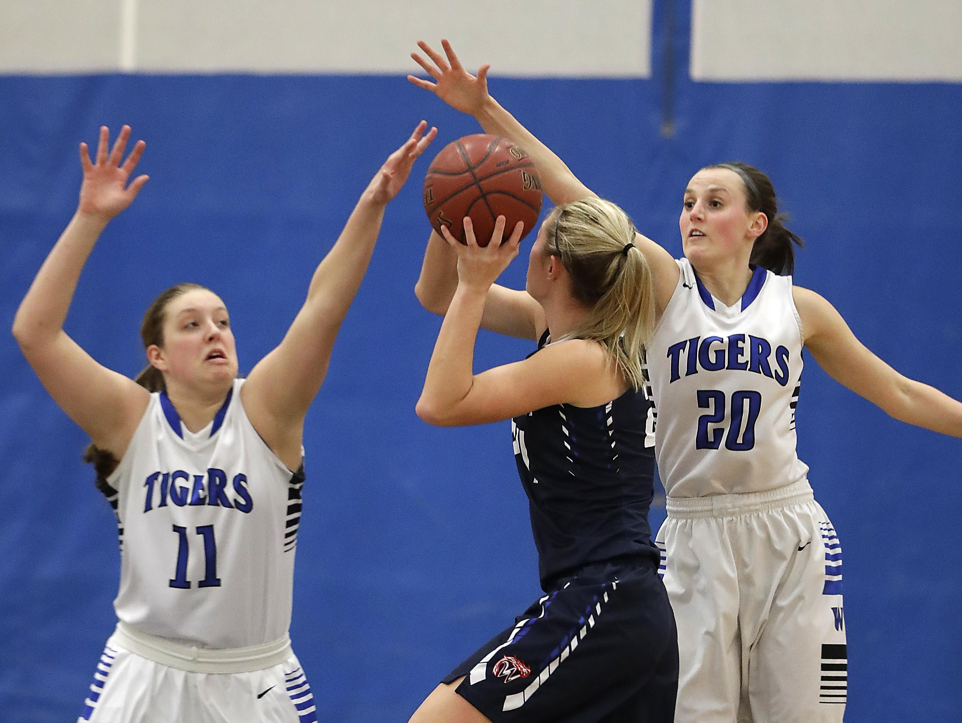 Wrightstown defenders Taylor Guns and Danielle Nennig converge to stop Waupaca's Victoria Nowak at Wrightstown on Tuesday. The Tigers clinched the NEC title with the win. See more photos from the game at greenbaypressgazette.com.