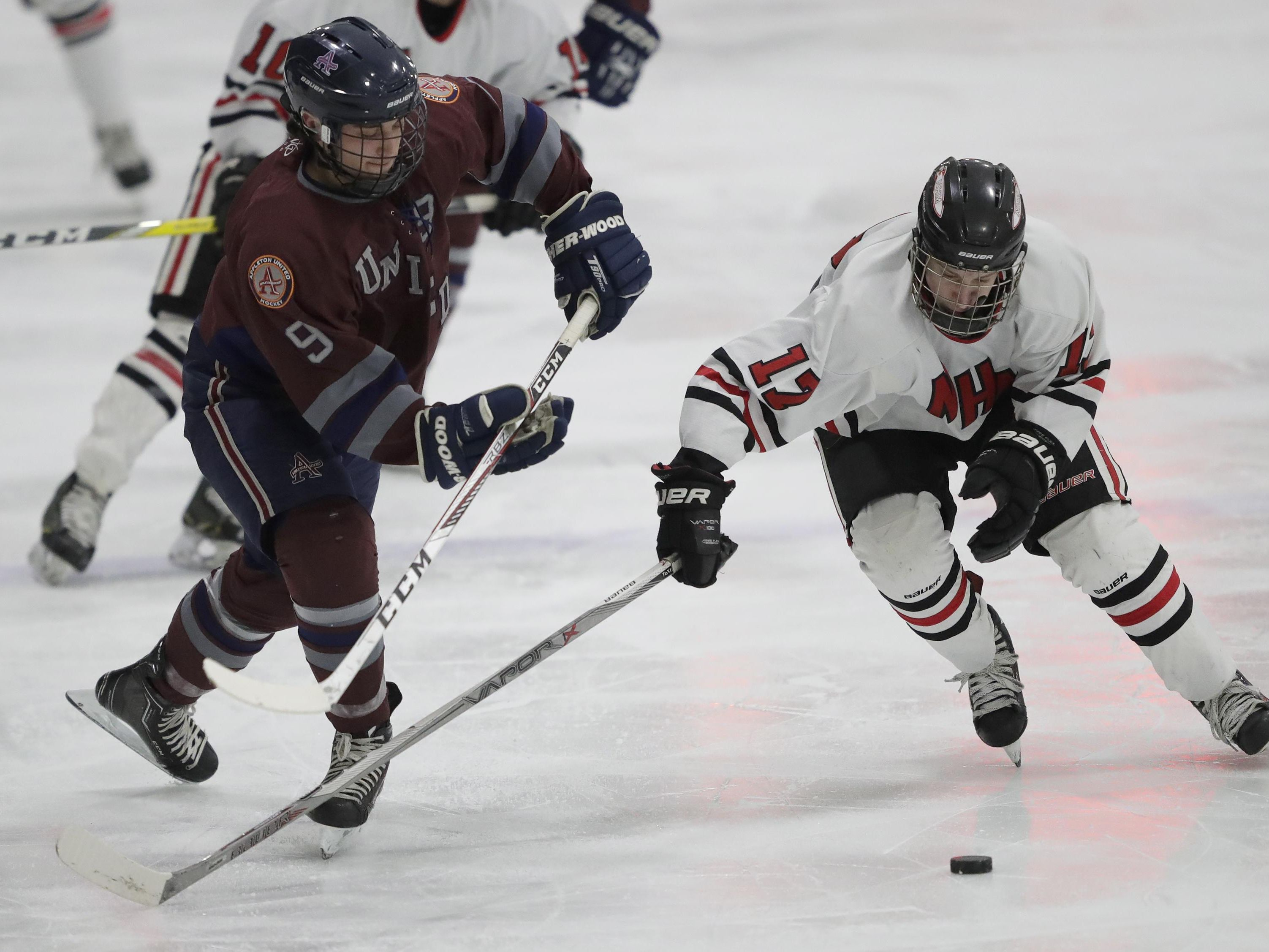 Appleton United's Mitchell Lund, left, battles for the puck against Neenah/Hortonville/Menasha's Eric Alberts on Tuesday.