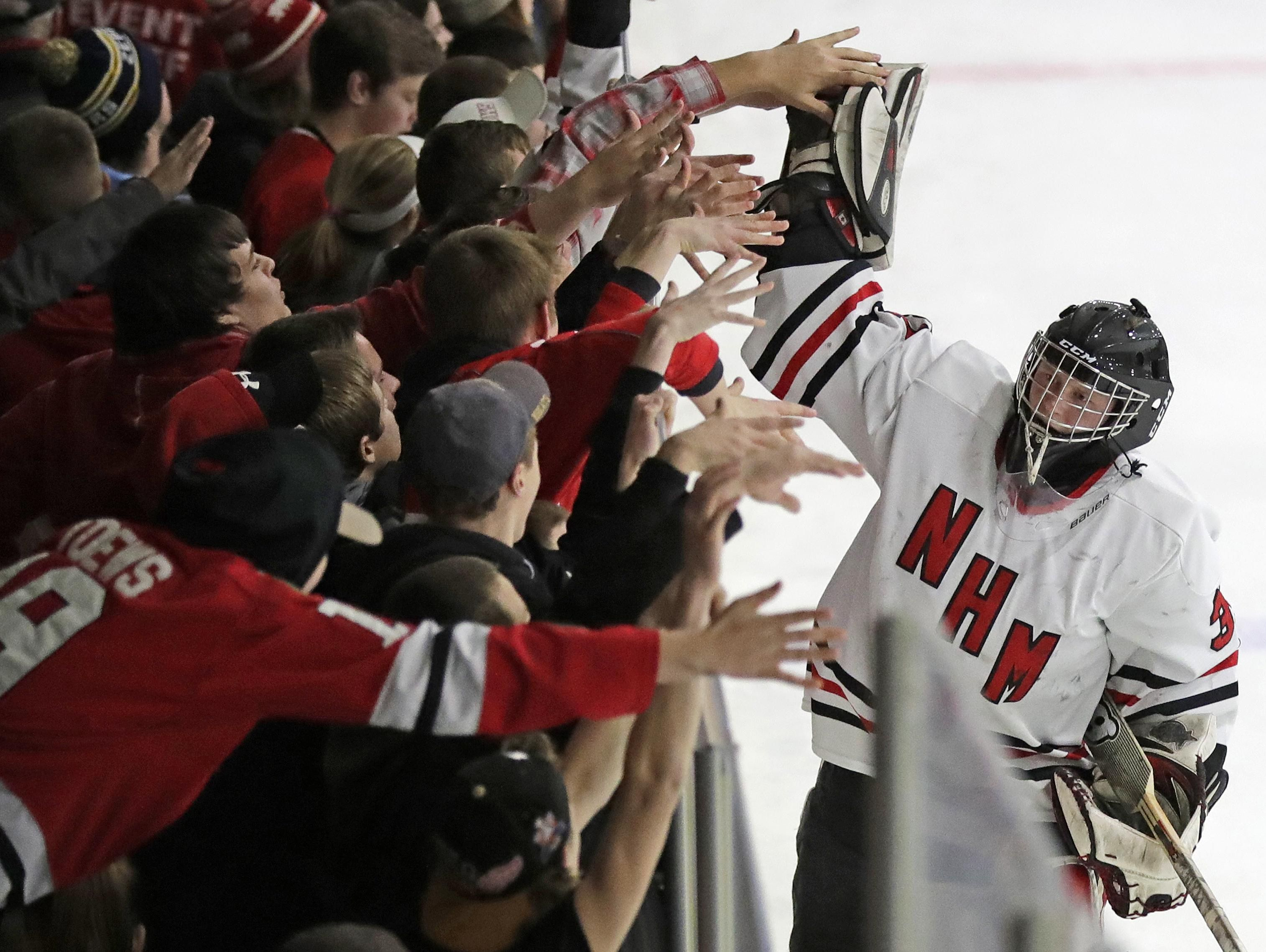 Neenah/Hortonville/Menasha goalie Preston Long high-fives fans after his team defeated Appleton United 4-0 on Tuesday in a WIAA sectional semifinal game at Tri-County Ice Arena in Fox Crossing. Long had 28 saves on the night.