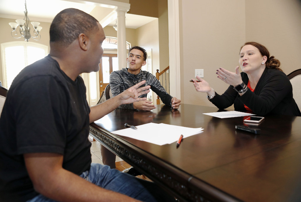 Trae Young (middle) discusses the pros and cons of his recruitment with his mom (right) and dad (left). (Photo: Alonzo Adams/USA Today Sports Images)