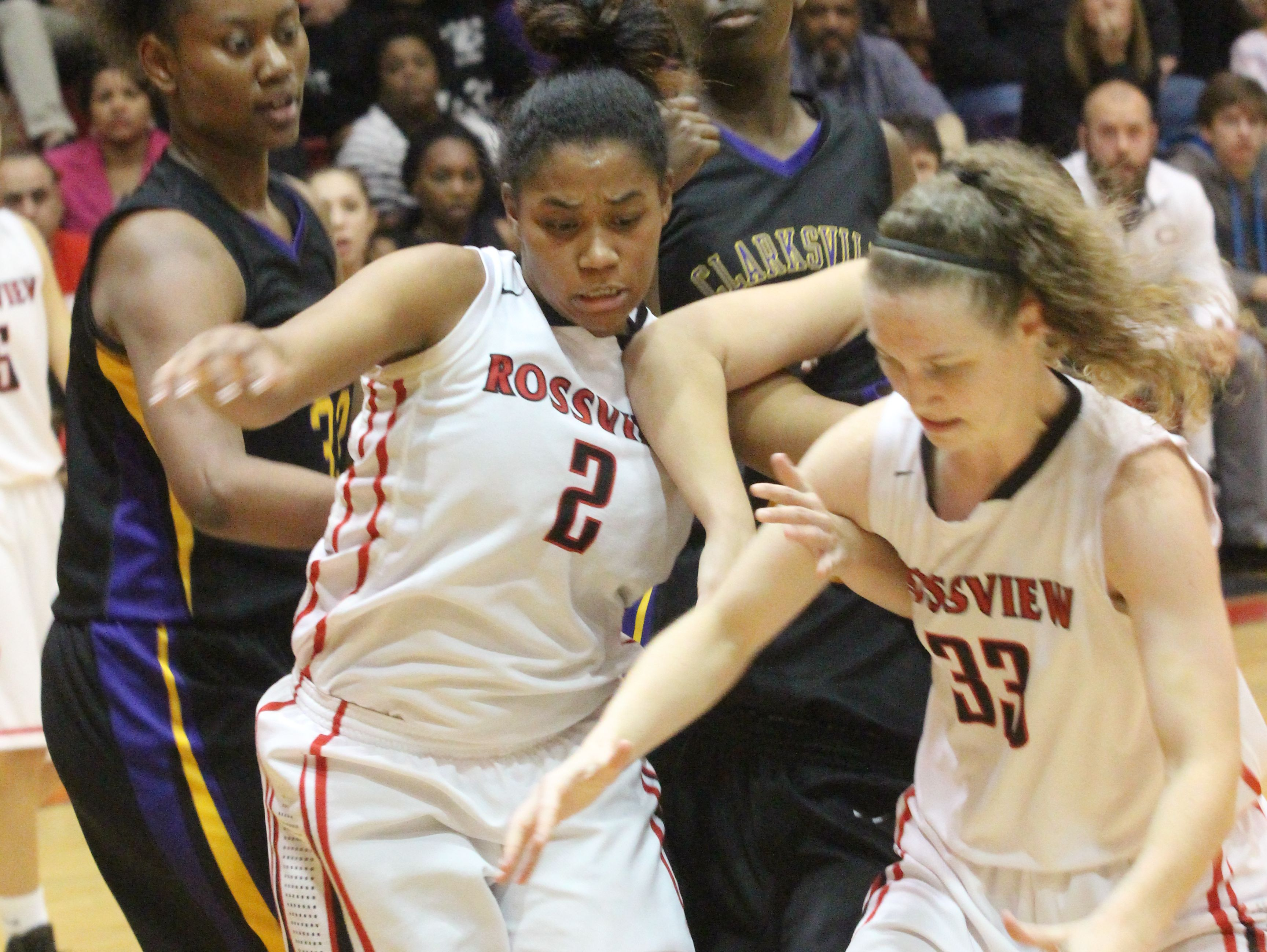 Rossview's Samajia Ogburn (2) and Liz Quinio (33) battle for the ball against Clarksville's Deja Wells and Chrislen Brown during the first half of their District 10 basketball game Tuesday.