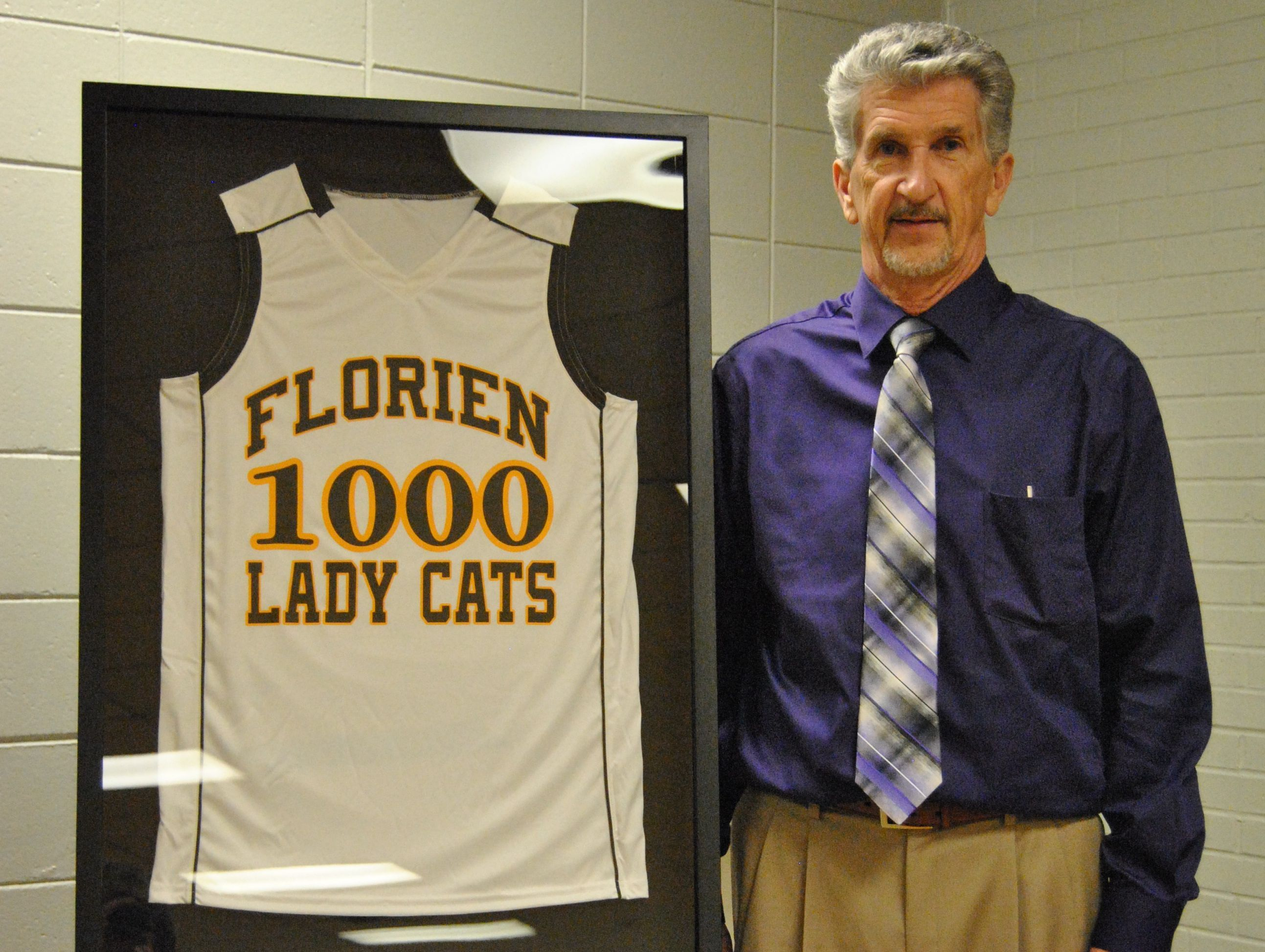 Florien's Dewain Strother poses with a jersey signifying his 1,000th career coaching victory.