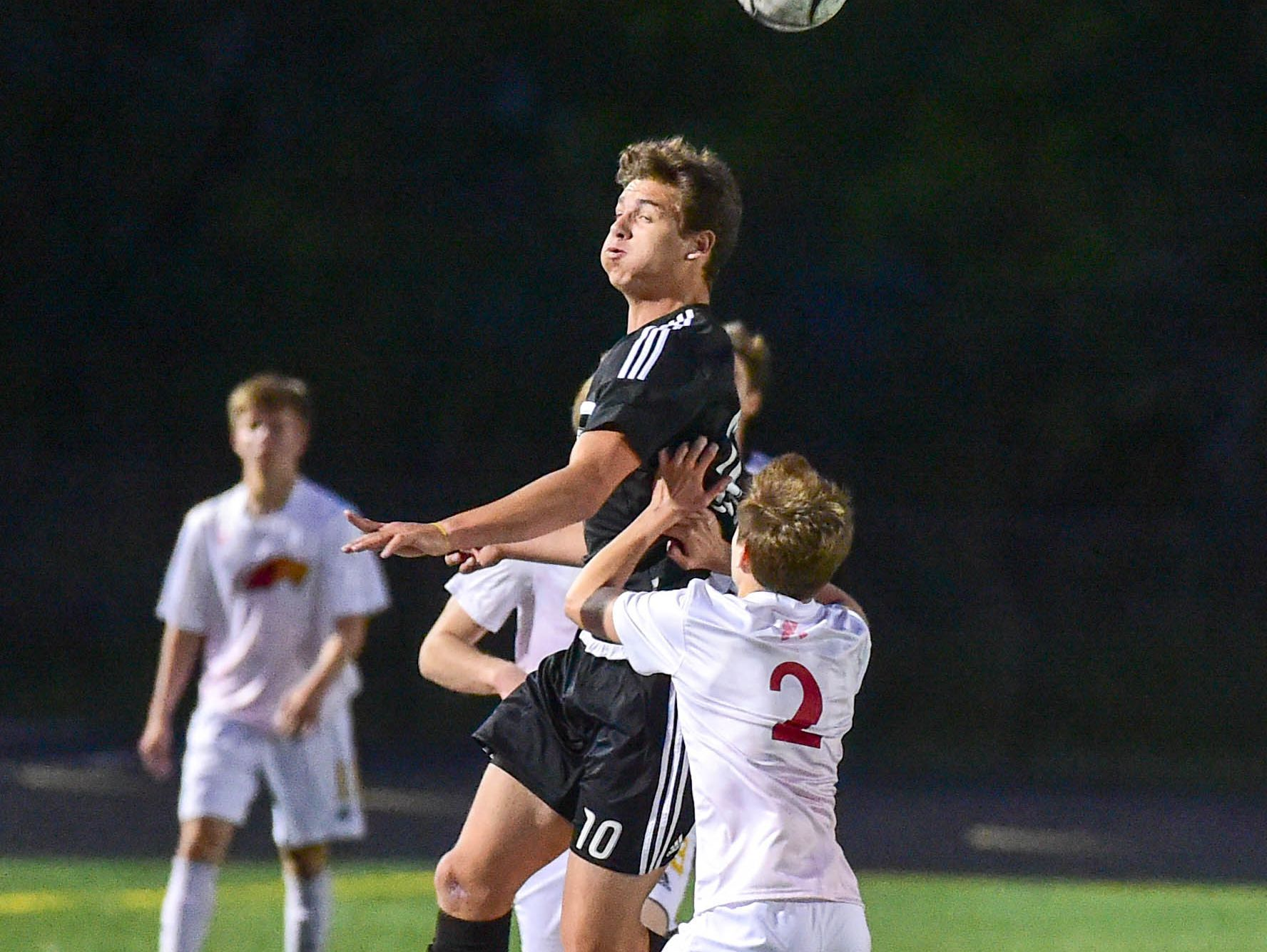 Ankeny Centennial's Jake Pinegar (10) heads the ball as Ankeny's Jack Nurre (2) defends on Thursday, May 5, 2016, during the Ankeny and Ankeny Centennial Soccer Doubleheader to Kick Out Cancer.The games and funds raised through t-shirt sales and PK (penalty kick) shootout ticket sales will support local Ankeny organization Cops Against Cancer.