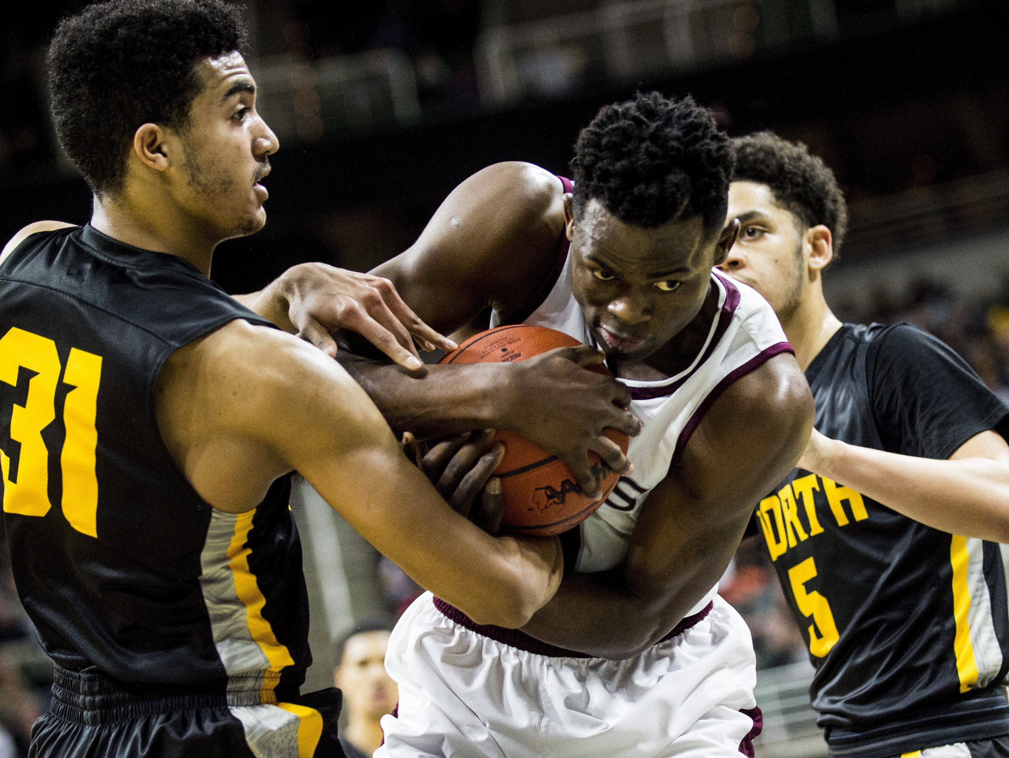 North Farmington defenders battle for a rebound with U-D Jesuit's Ikechukwu Eke, center, in a Class A boys high school basketball state championship game March 26, 2016, in East Lansing.