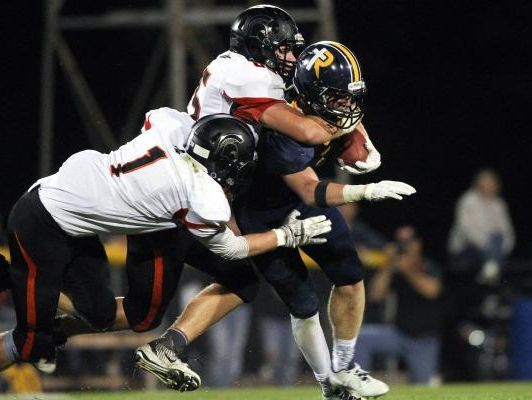 Solon's Tyler Linderbaum tackles Regina's Isaac Vollstedt during their game at Regina on Friday, Sept. 2, 2016.