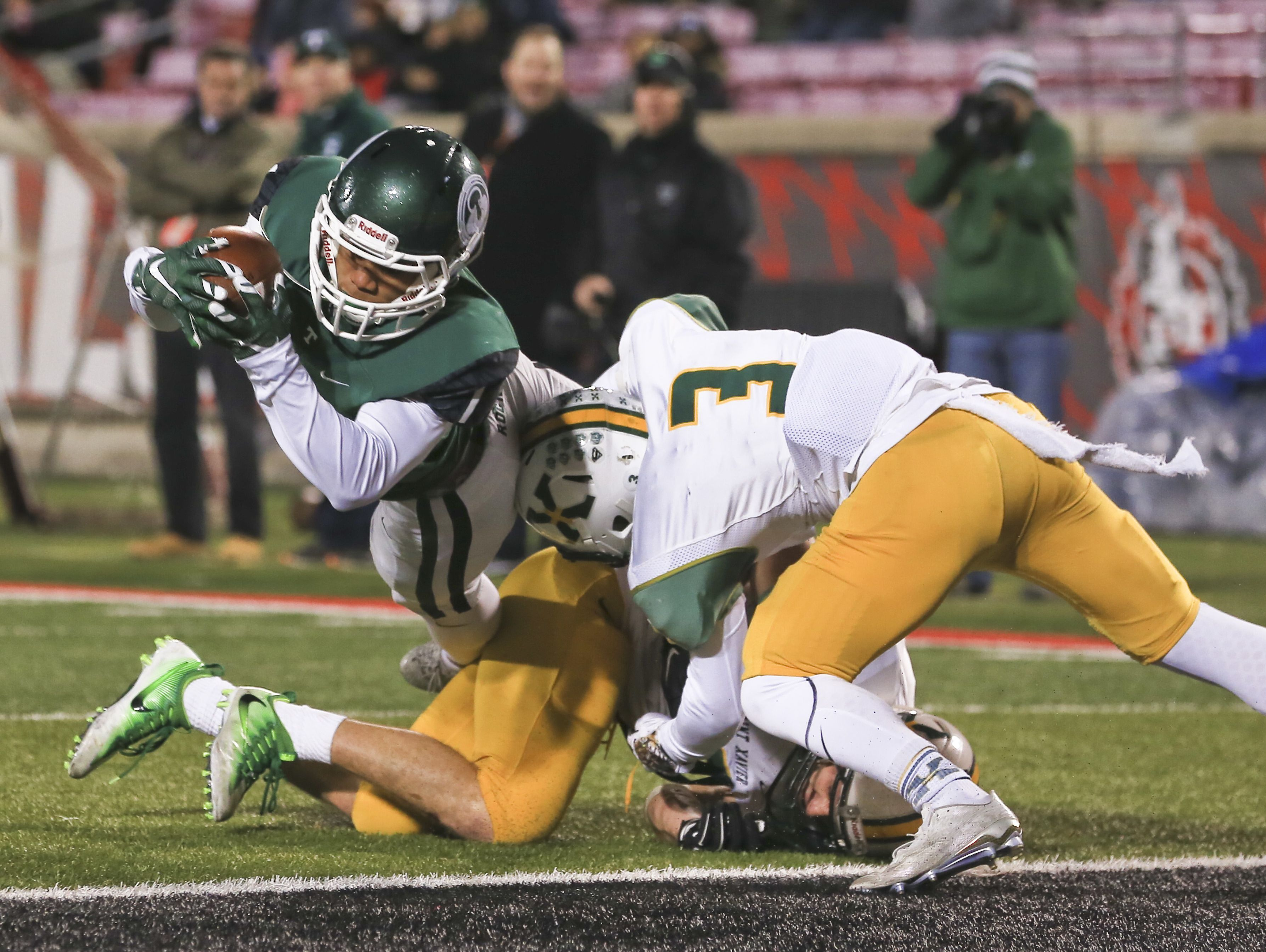 Trinity's Rondale Moore lunges over St. X's Jake Taylor (3) and Brandon Washburn to give the Rocks another touchdown in the third quarter as Trinity beat St. X 24-14 in the semi-state game Friday night at Papa John's Cardinal Stadium.