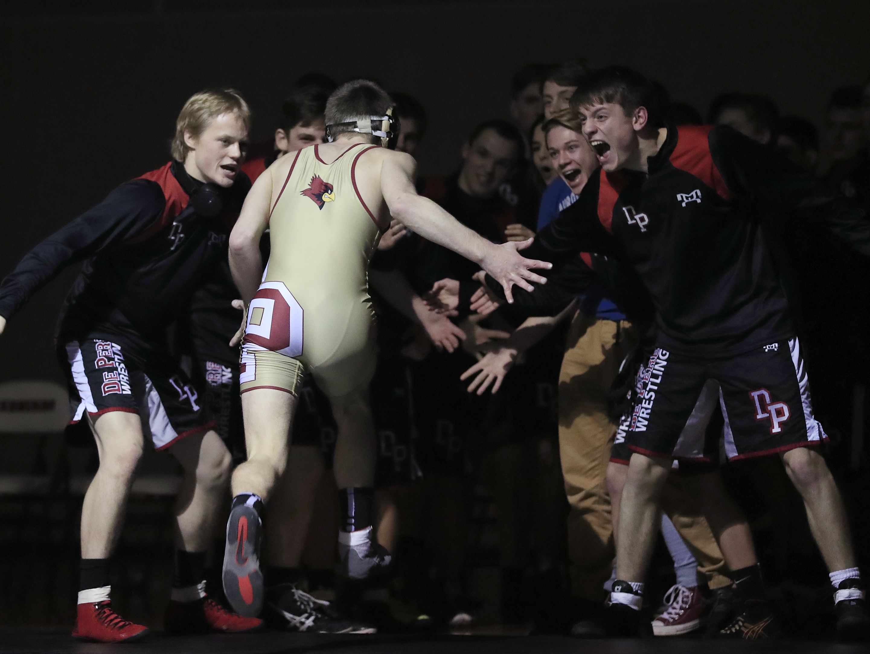 De Pere's Max Bruss runs to his teammates after pinning Pulaski's Brock Gracyalny in the 138-pound bout of a Fox River Classic Conference dual at De Pere on Jan. 19.