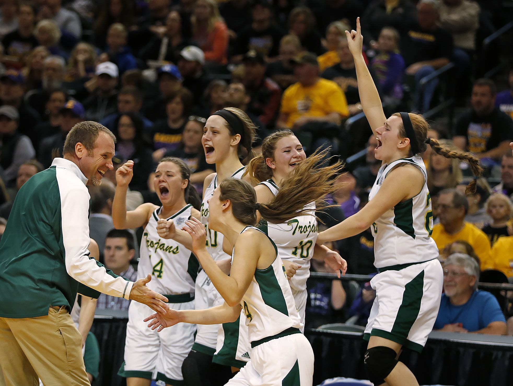 Wood Memorial coach Johnnie Bartley (left) and his players celebrate their victory in the 2017 IHSAA Class A Girls Basketball State Finals on Saturday in Indianapolis at Bankers Life Fieldhouse. Wood Memorial beat Union City 68-43.