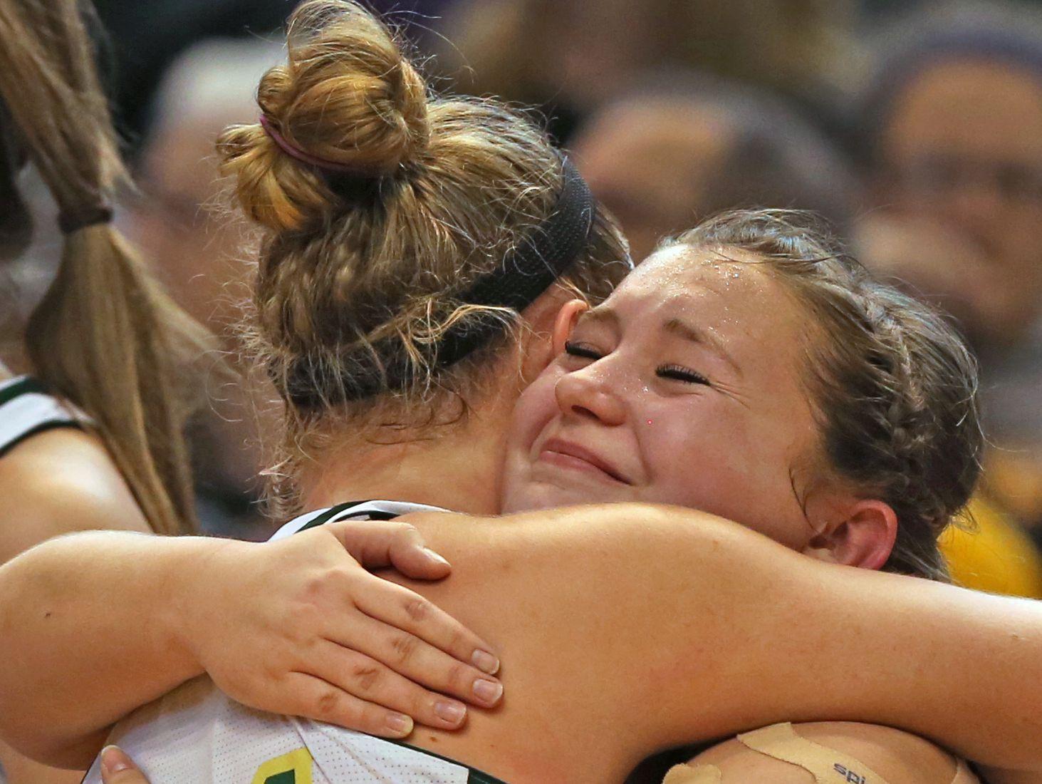 Brenna Maikranz, left, hugs teammate Carsen Robinson after Wood Memorial won the 2017 IHSAA Class A Girls Basketball State Finals, Saturday.