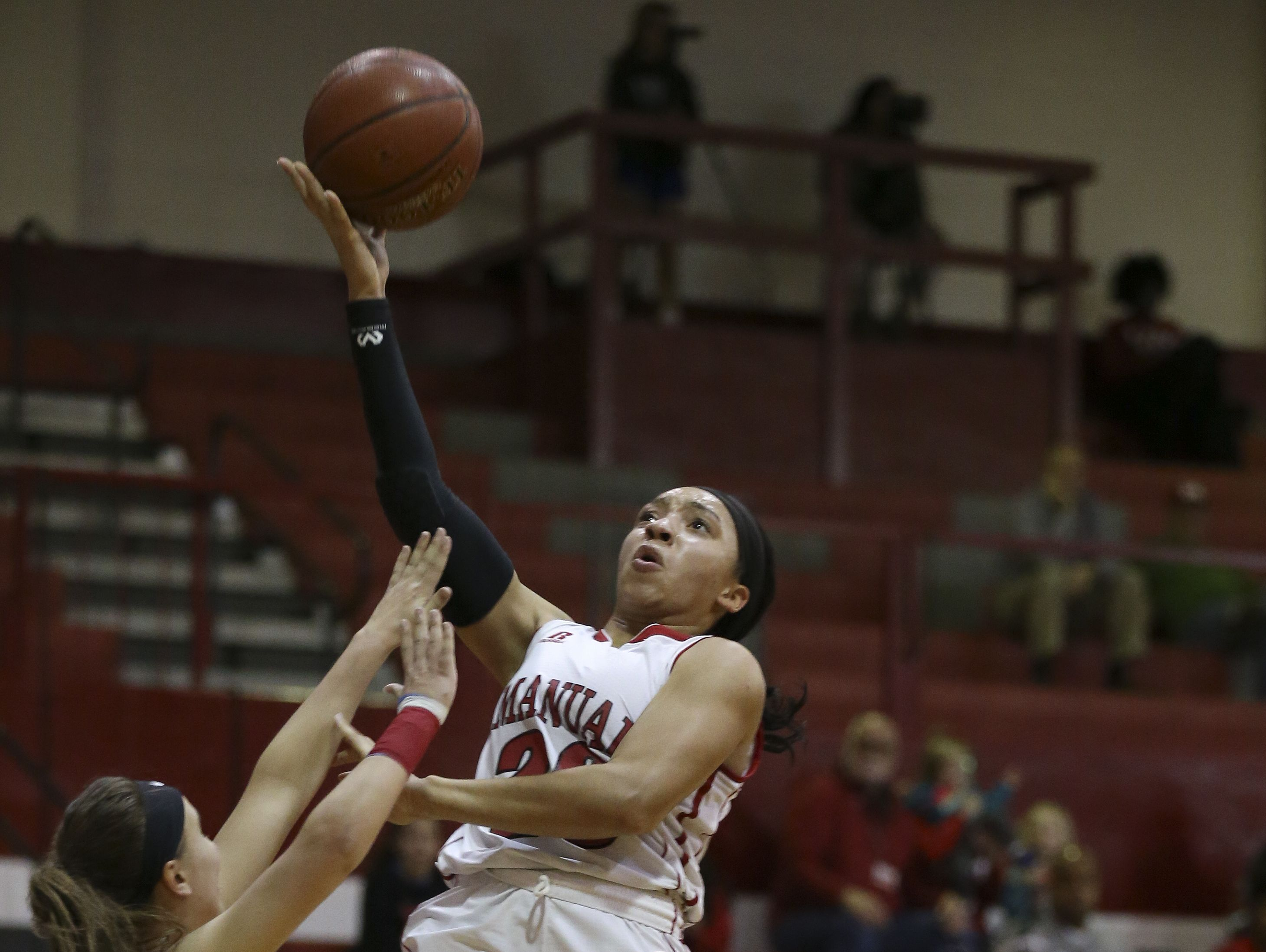 Manual's Tonysha Curry (23) shoots against the defense of CAL's Summer Conti (10) during their game at Manual. Feb. 27, 2017