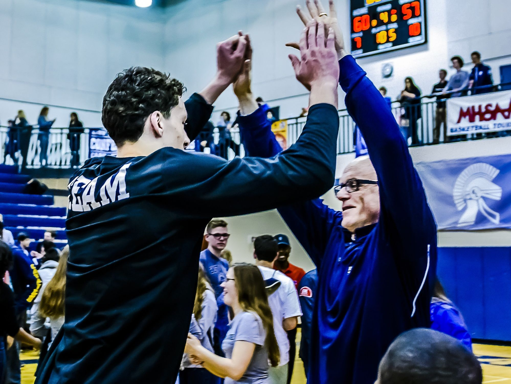 Brandon Johns, left, of East Lansing high-fives Finamore last season after winning the Class A district title. Finamore led the Trojans to a 23-1 record in 2015.
