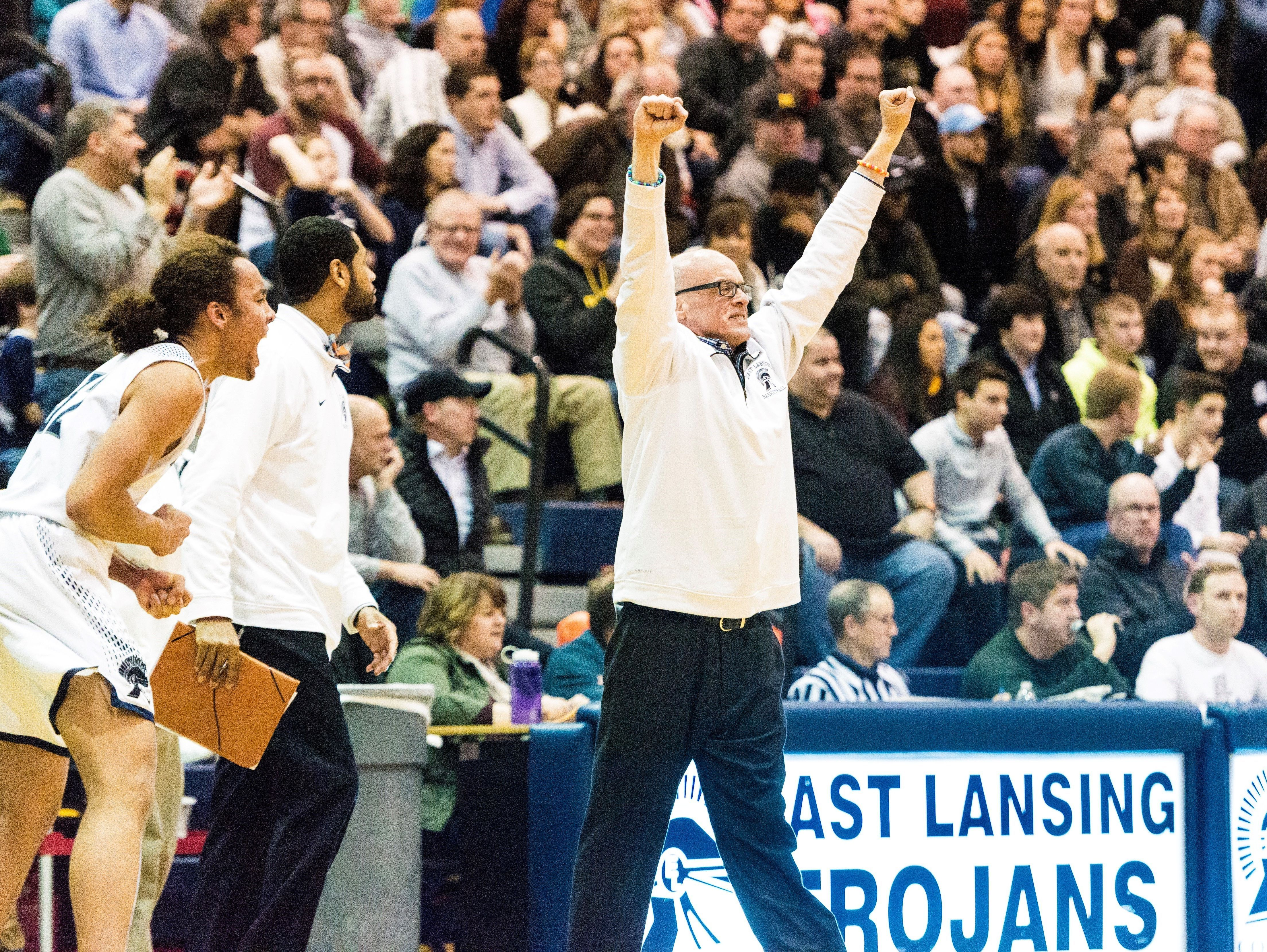 East Lansing coach Steve Finamore celebrates after a Brandon Johns dunk gave his team a 67-63 lead with 21 seconds left in a game against Holt on Jan. 13 in East Lansing.