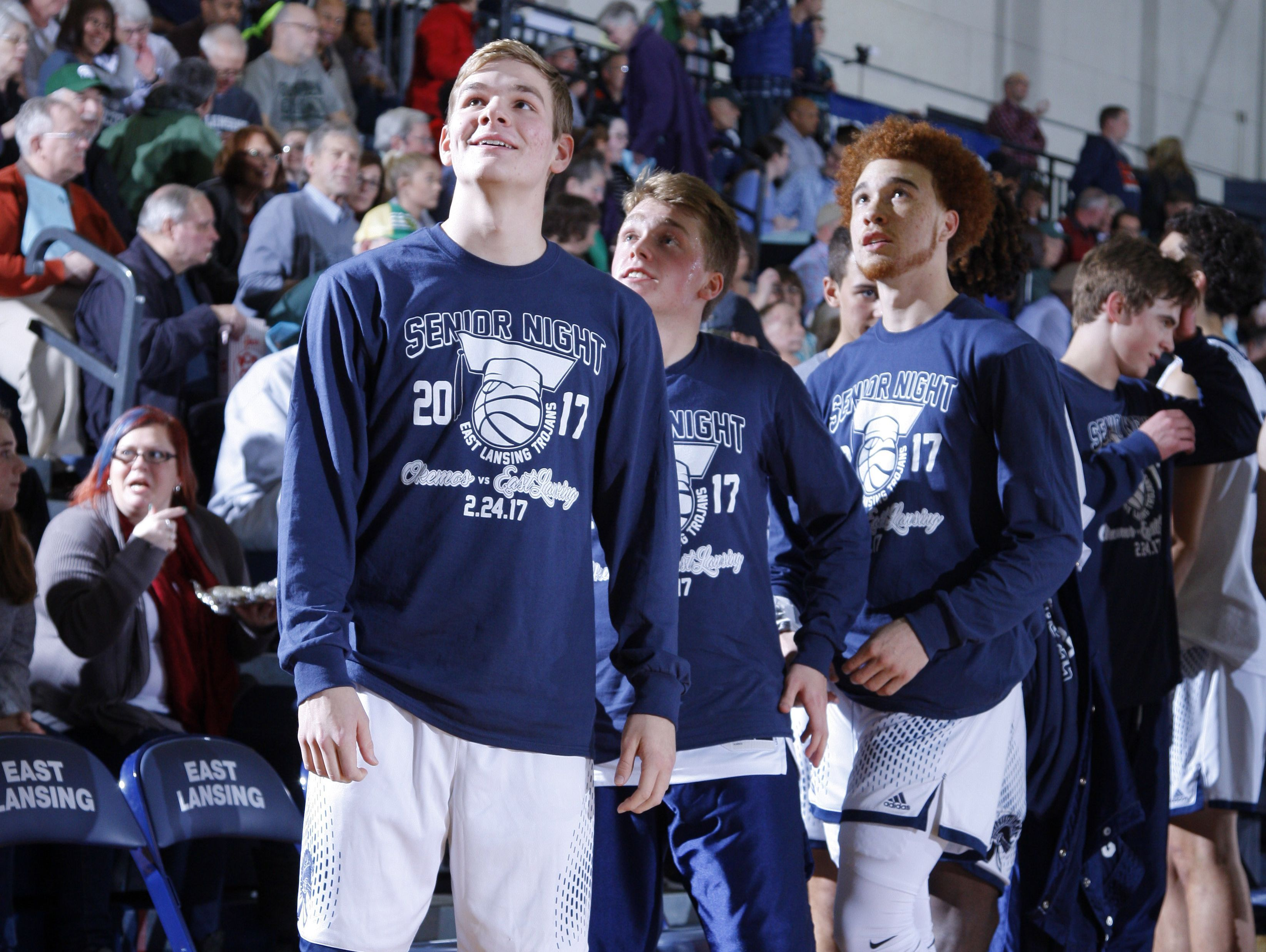 East Lansing senior Caleb Hoekstra, left, who suffered a broken foot earlier in the season, stands with teammates before a senior day game against Okemos Friday, Feb. 24, 2017, in East Lansing, Mich.