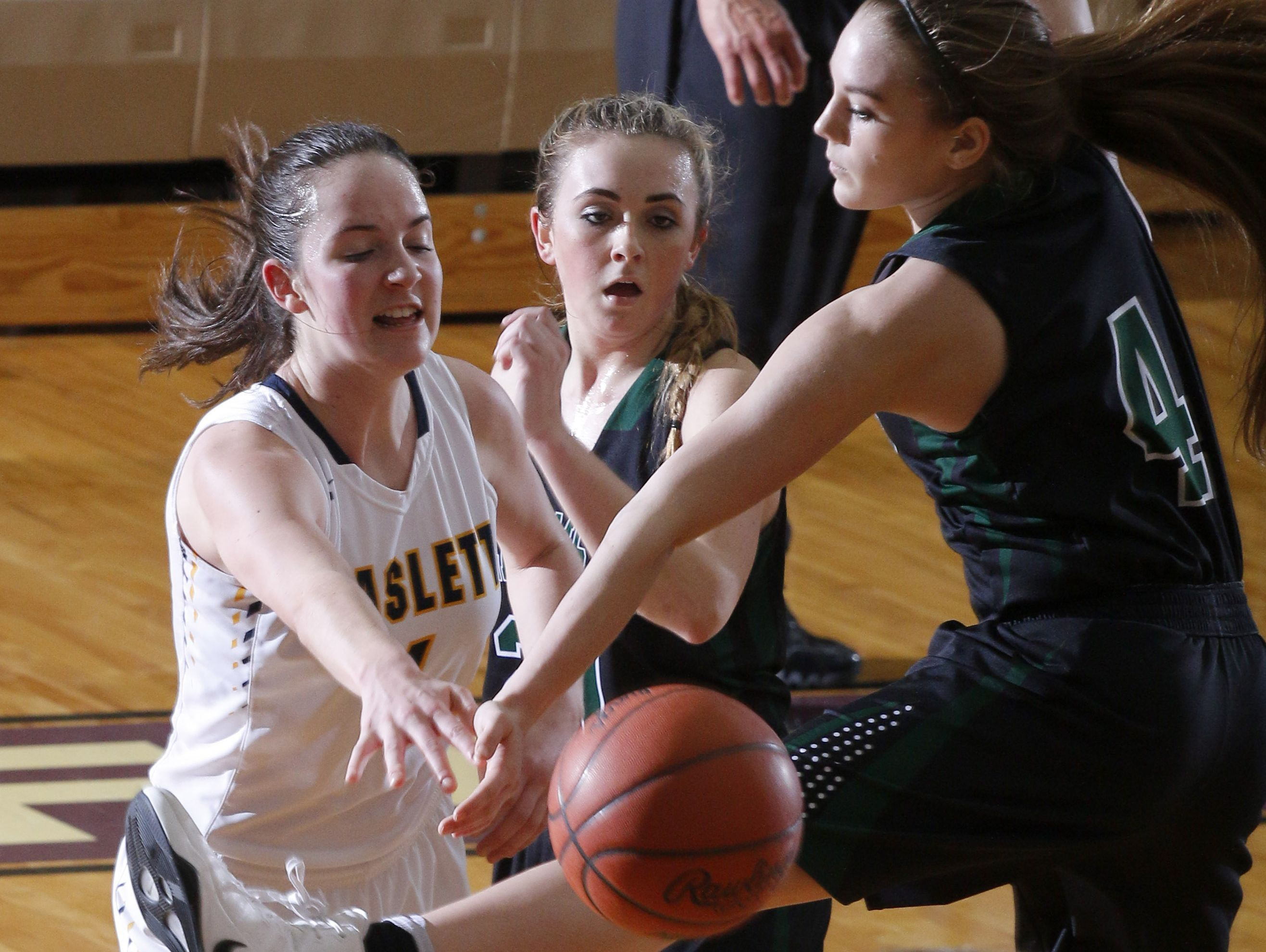 Williamston's Maddie Watters, right, tries to deflect a pass by Haslett's Ella McKinney, left, as Williamston's Halle Wisbiski, center, watches during their district semifinal game Wednesday, March 1, 2017, in Fowlerville, Mich. Williamston won 53-42.