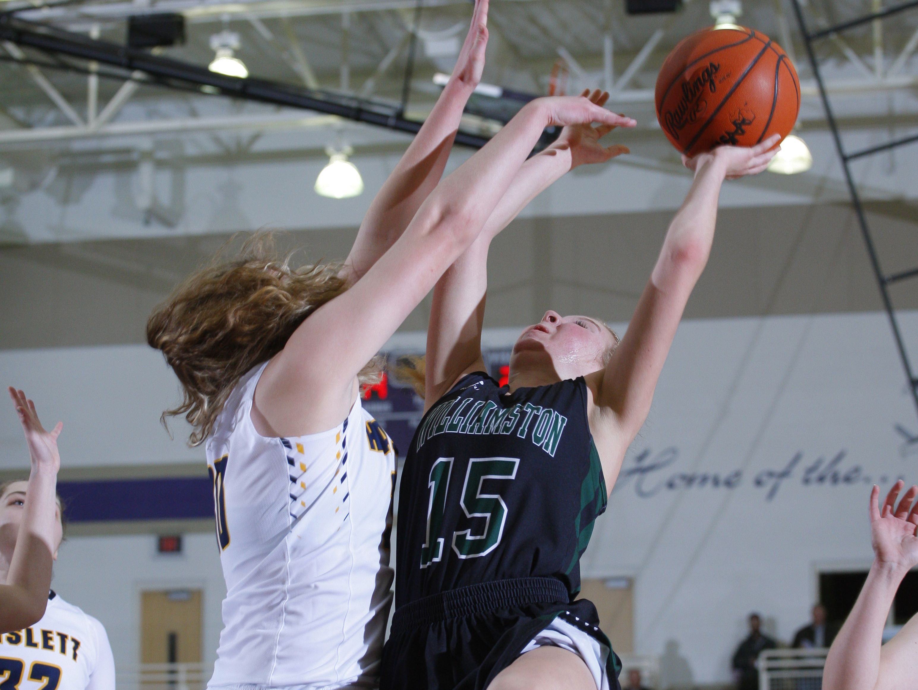 Williamston's Elana Lycos, right, puts up a shot against Haslett's Sydnee Dennis during their district semifinal game Wednesday, March 1, 2017, in Fowlerville, Mich. Williamston won 53-42.